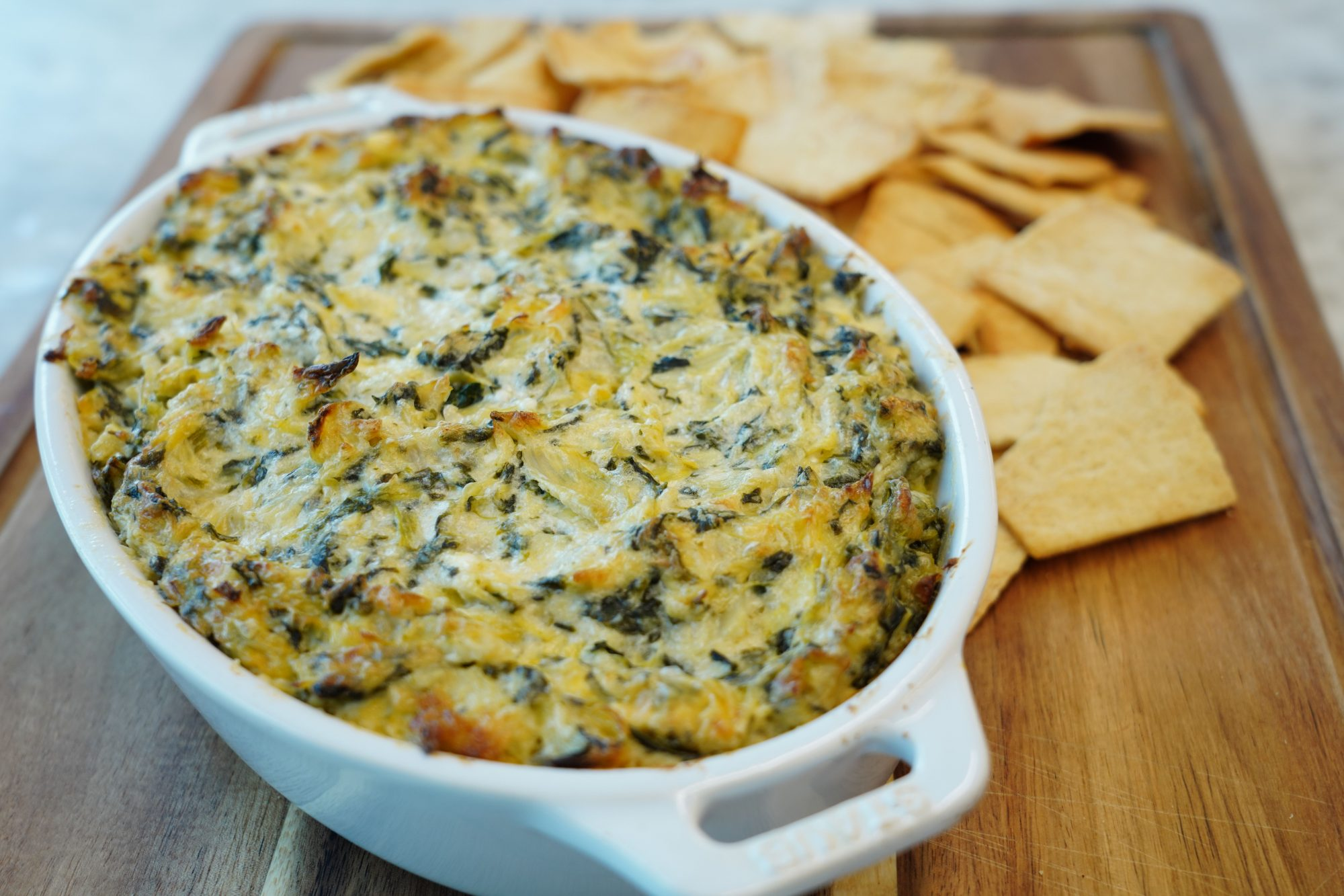 Baking dish filled with homemade Luscious Spinach Artichoke Dip recipe served with pita chips