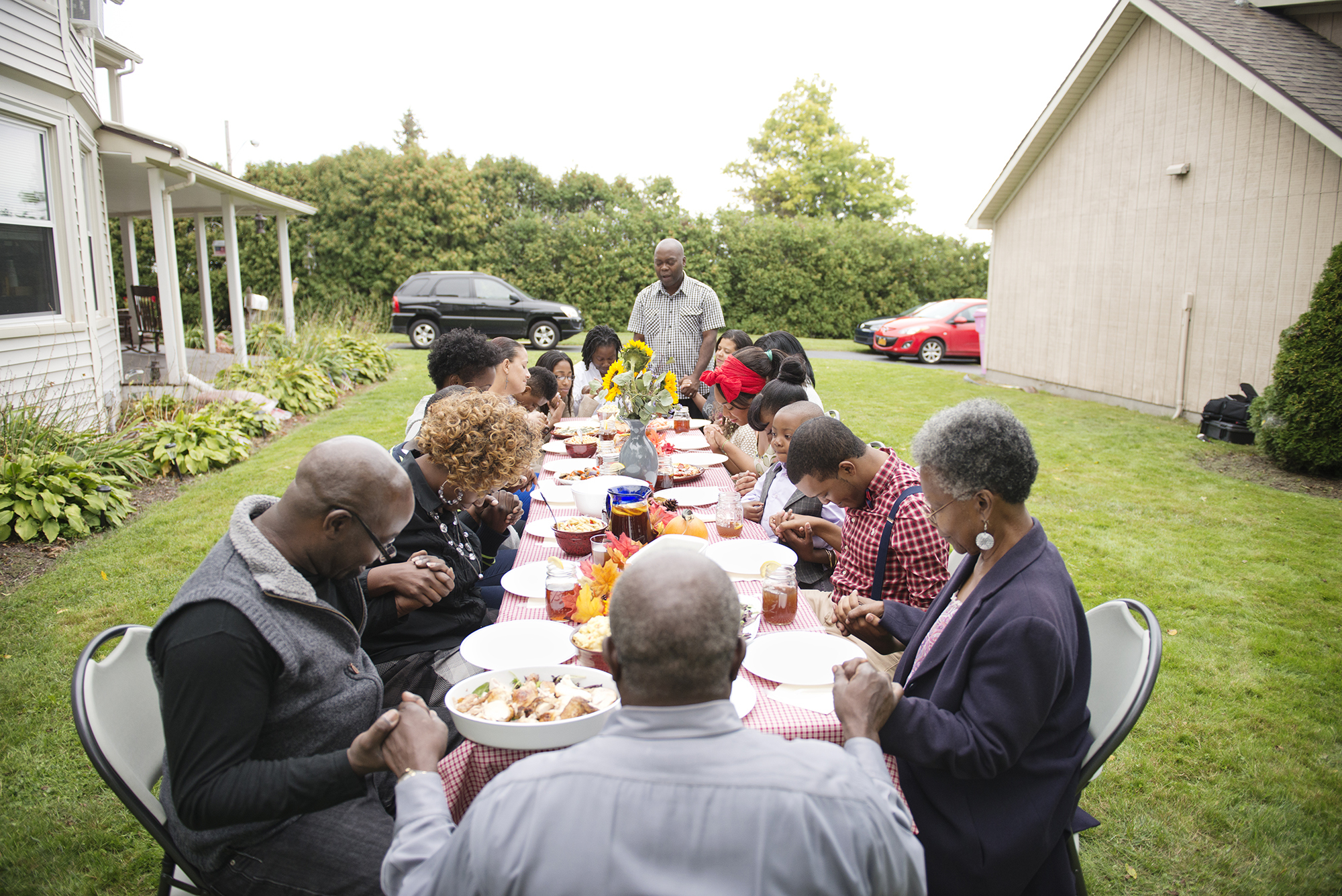 black family gathered in prayer around food-filled outdoor table