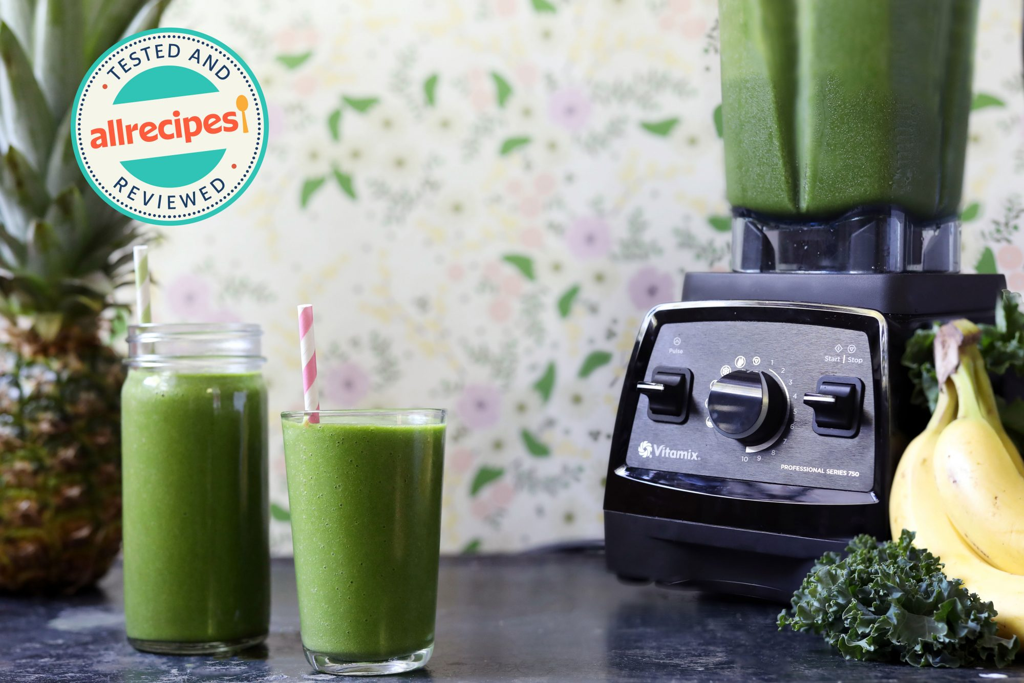 vitamix with green smoothie inside next to banana, kale, pineapple, and two green smoothies in glasses