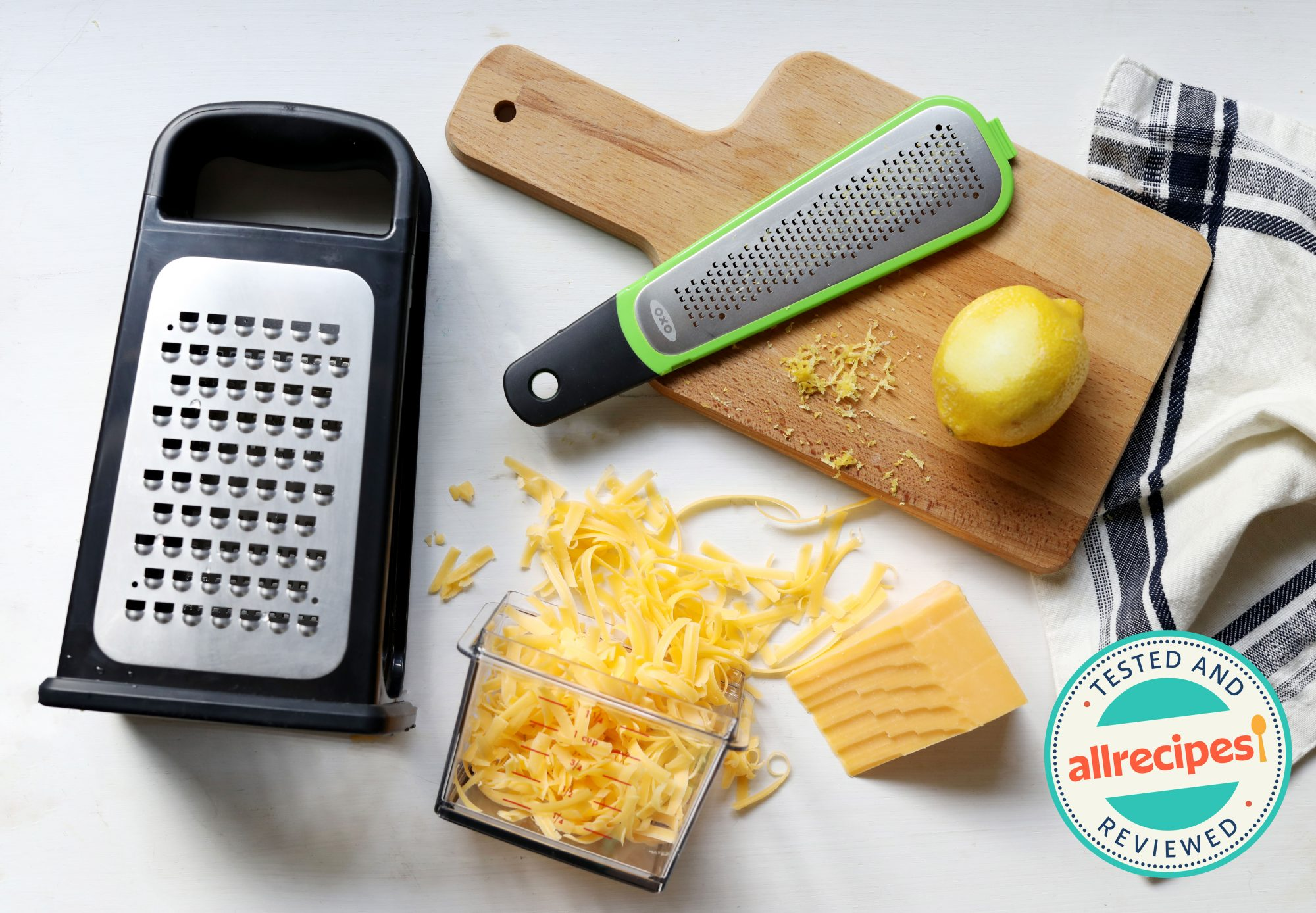 box graters, cheddar cheese, cutting board, dish towel, and zested lemon