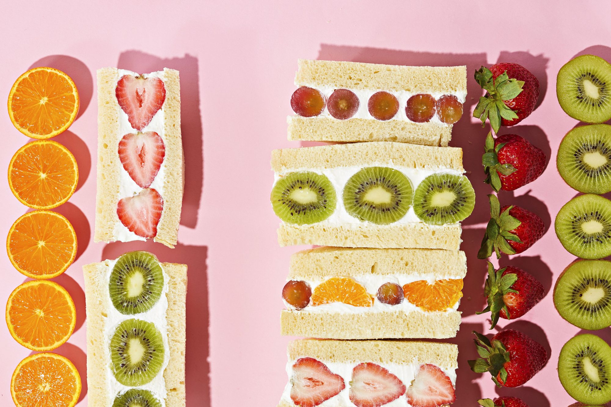 Fruit sandwiches lined up on a pink background.