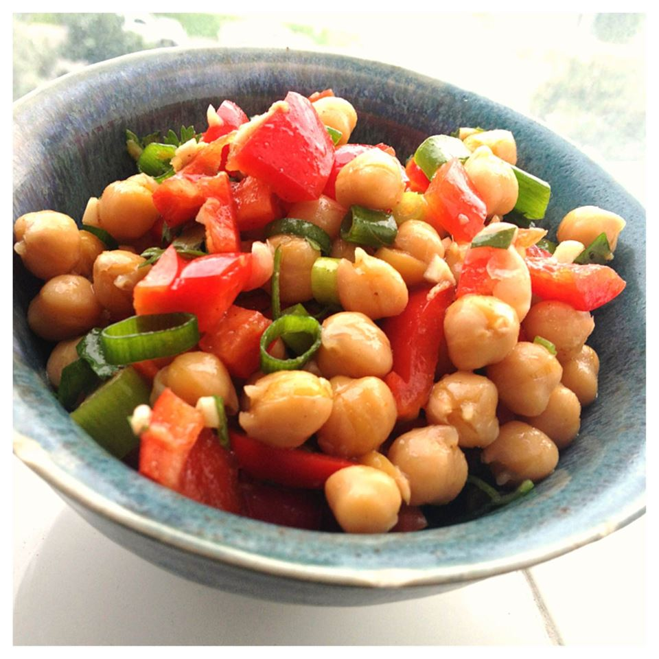 Bowl of homemade Cumin and coriander Chickpea Salad with bell peppers, green onion, and garbanzo beans