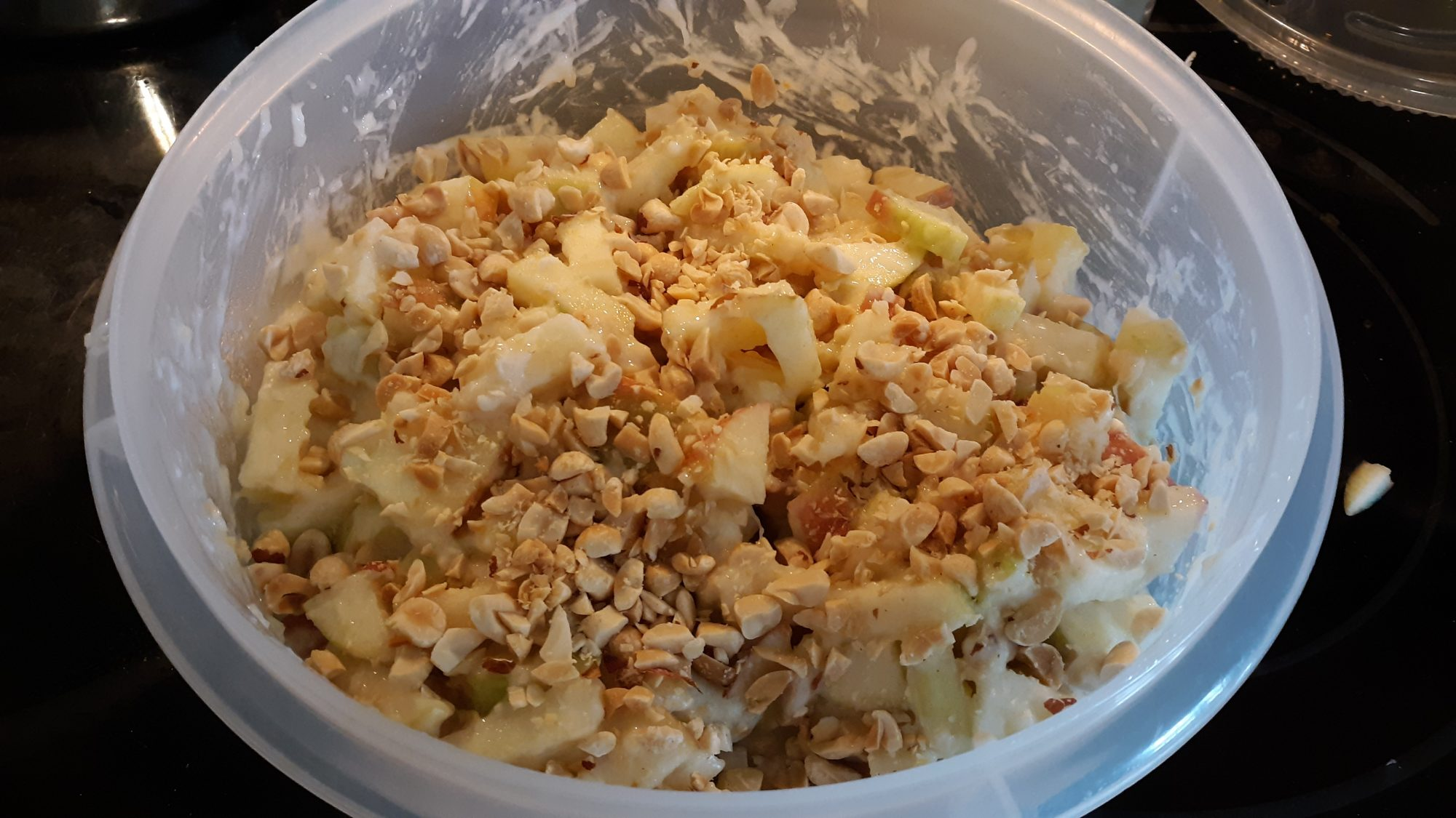 bowl of homemade Candy Apple Salad recipe with chopped apple, pineapple, and peanuts