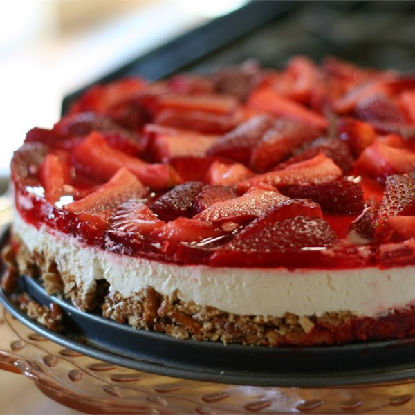 side view of a dessert made in a springform pan showing the layers of pretzel crust, cream cheese layer, and strawberry gelatin and fresh strawberry topping