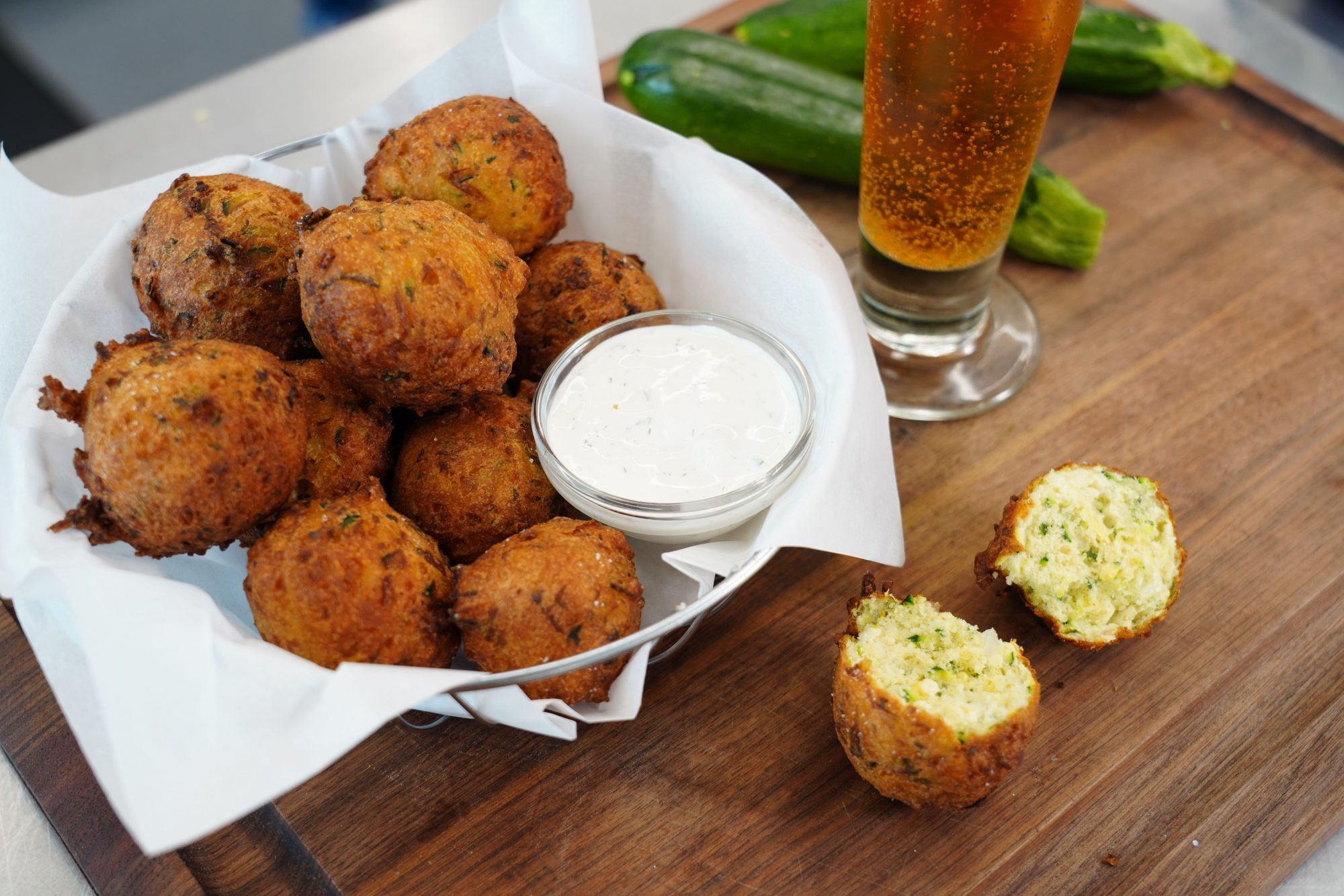 bowl of fried Zucchini Puffs recipe with ranch dressing dipping sauce and a glass of beer