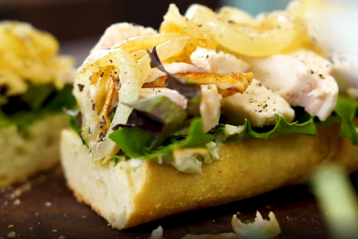 toasted baguette topped with pesto mayonnaise, arugula, sliced chicken, and caramelized onions