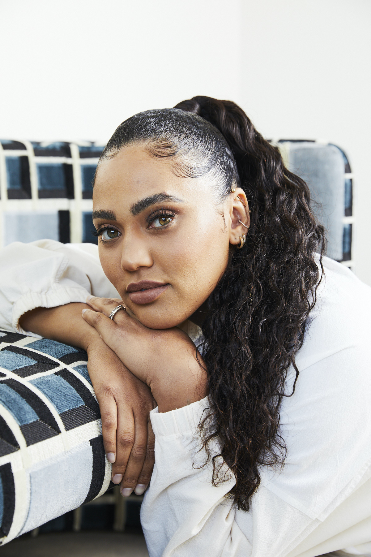 Ayesha Curry resting head on hands on a couch