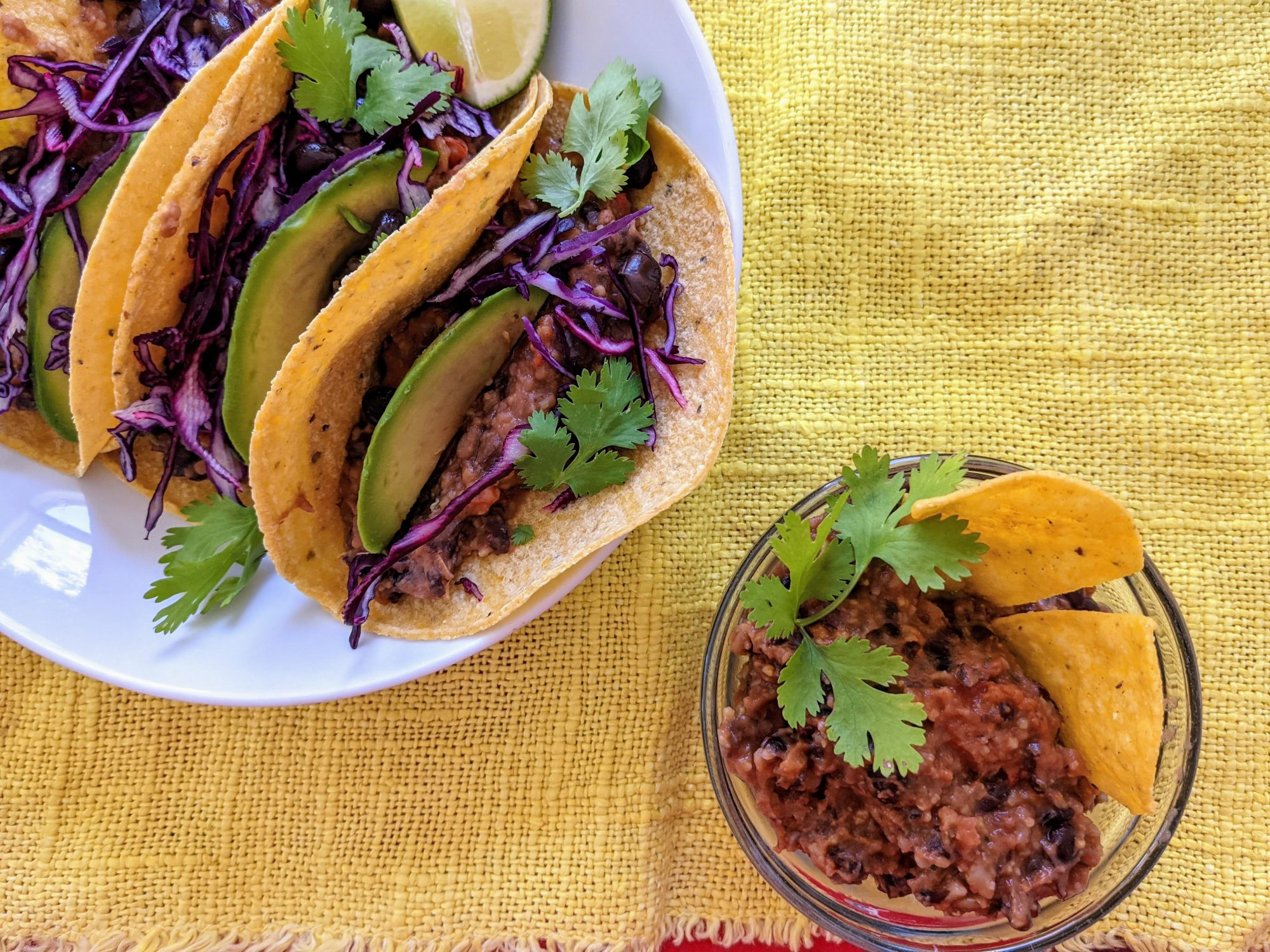 vegan bean taco filling, in a bowl with chips for dipping as well as in tacos on a platter.