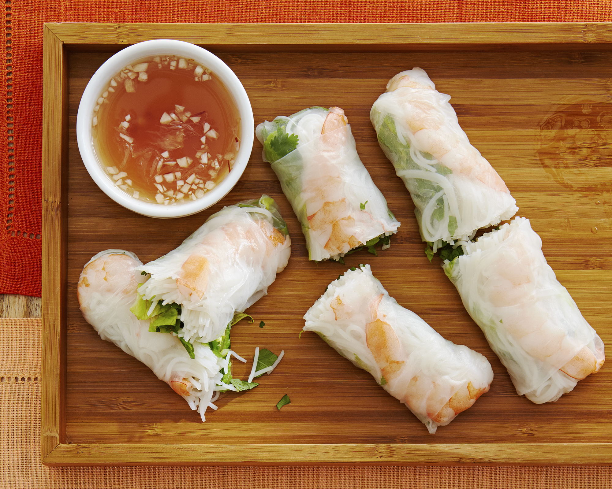 An overhead view of 3 Vietnamese Spring rolls, cut in half, on a bamboo tray. Served with a chili sauce