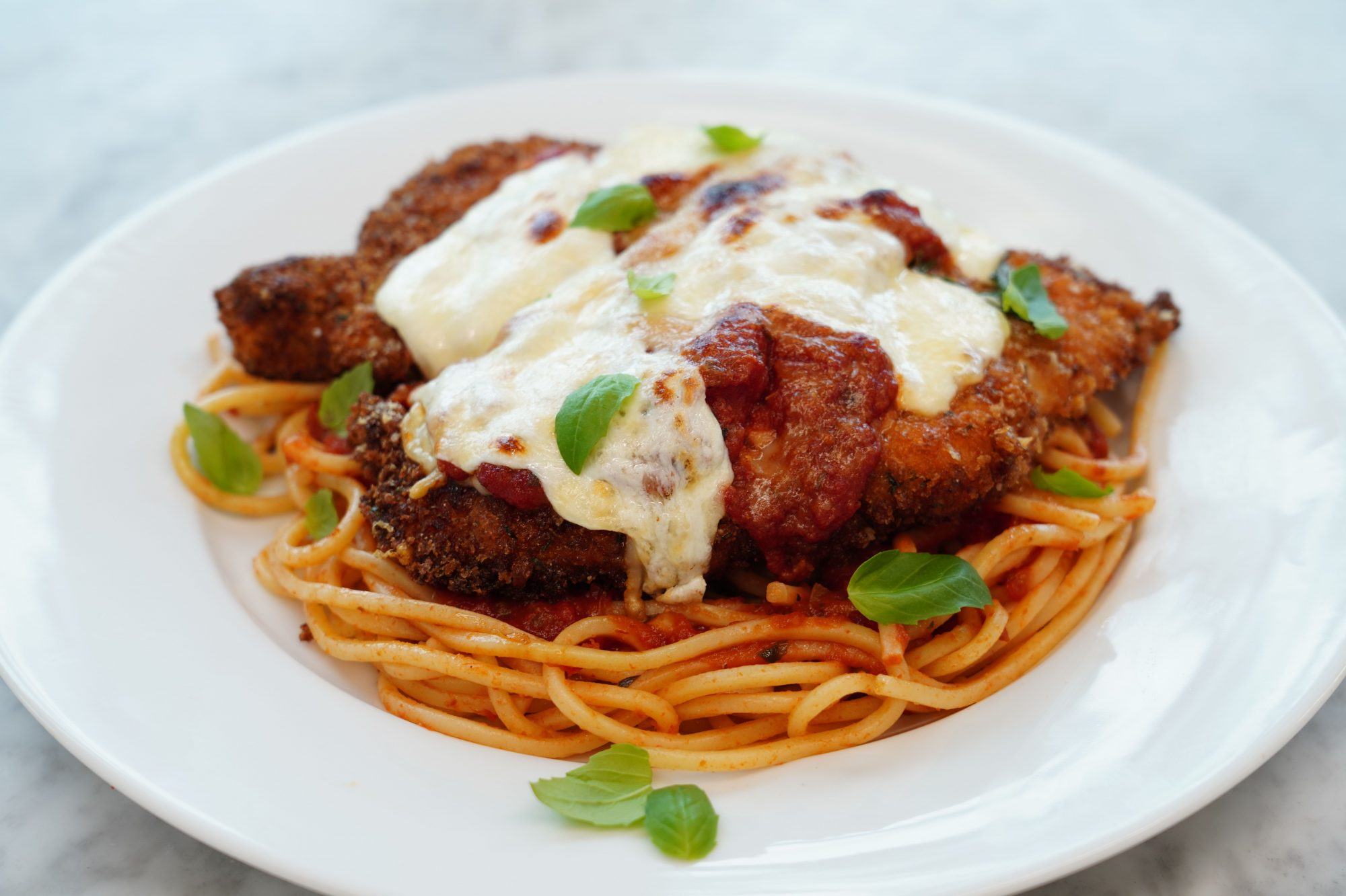 homemade chicken parmesan recipe served on spaghetti and garnished with fresh basil leaves