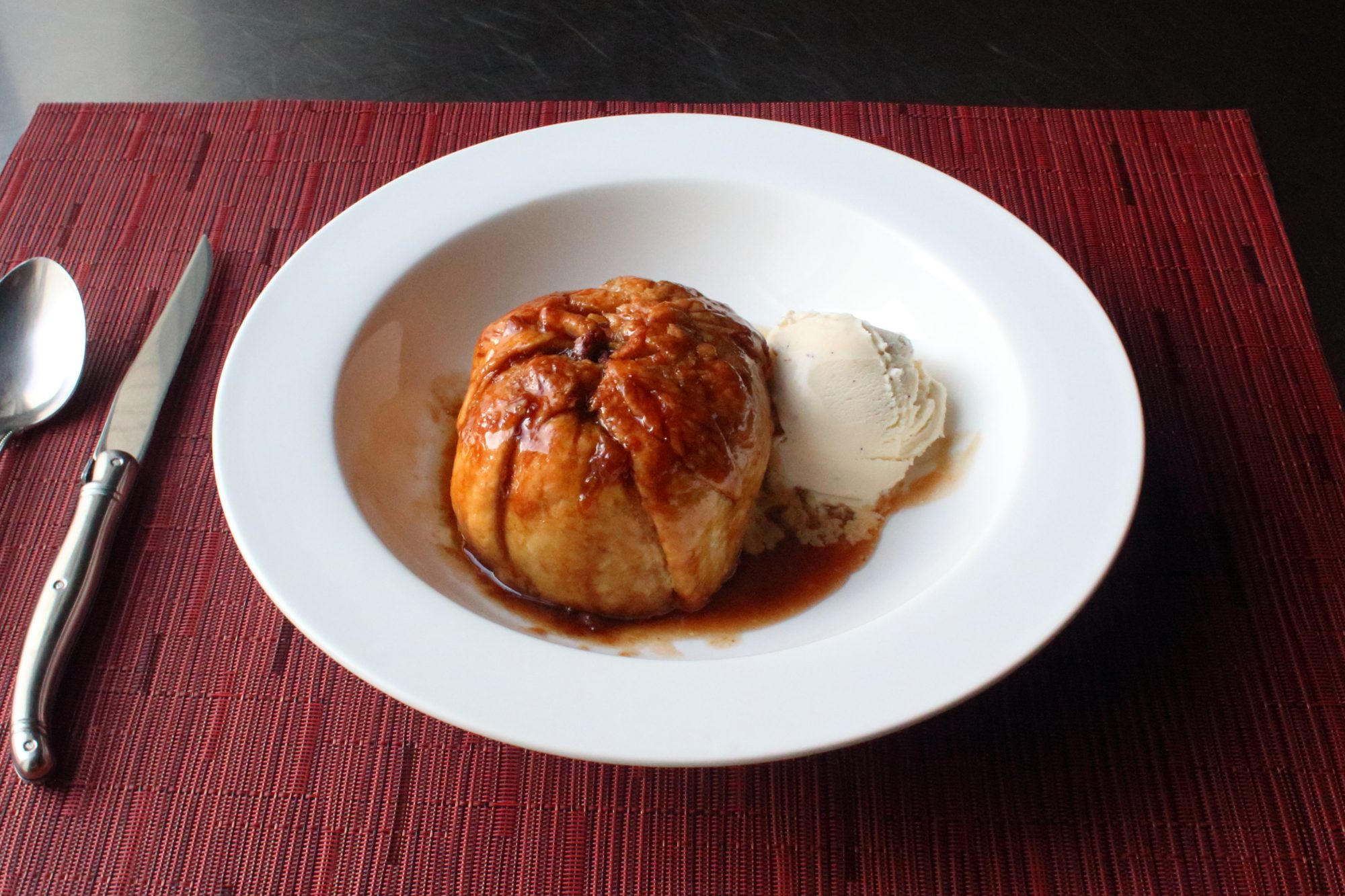 apple dumpling with sauce and ice cream in bowl
