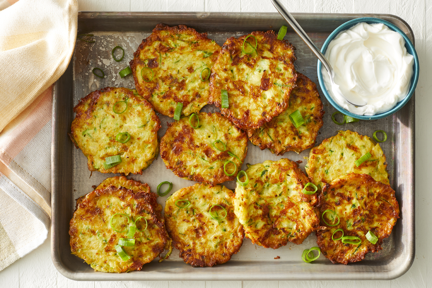 A tray of fresh of the stove zucchini patties. Garnished with sliced green onions and a side of sour cream