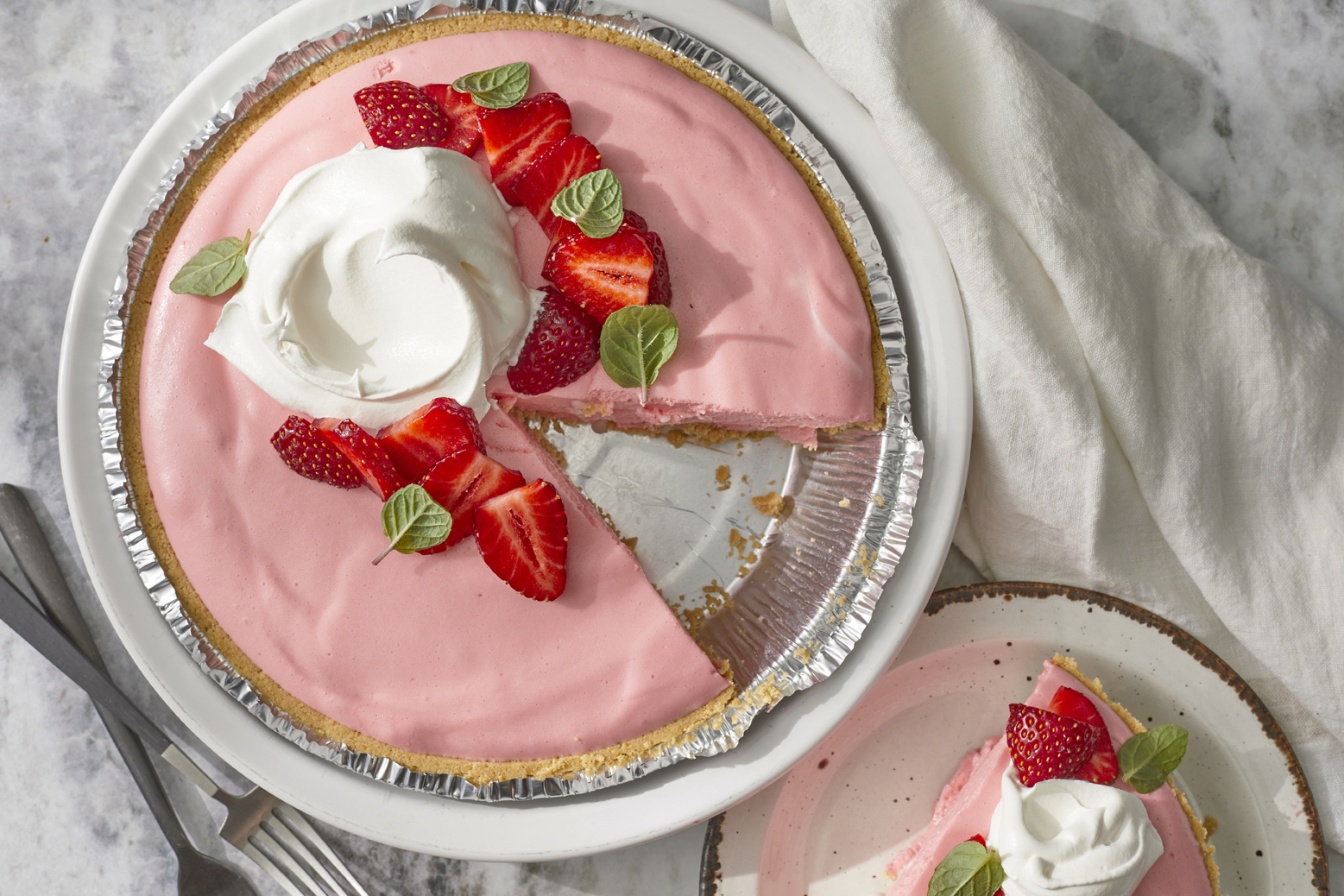 overhead view of a no bake strawberry cheesecake topped with whipped cream and fresh strawberries