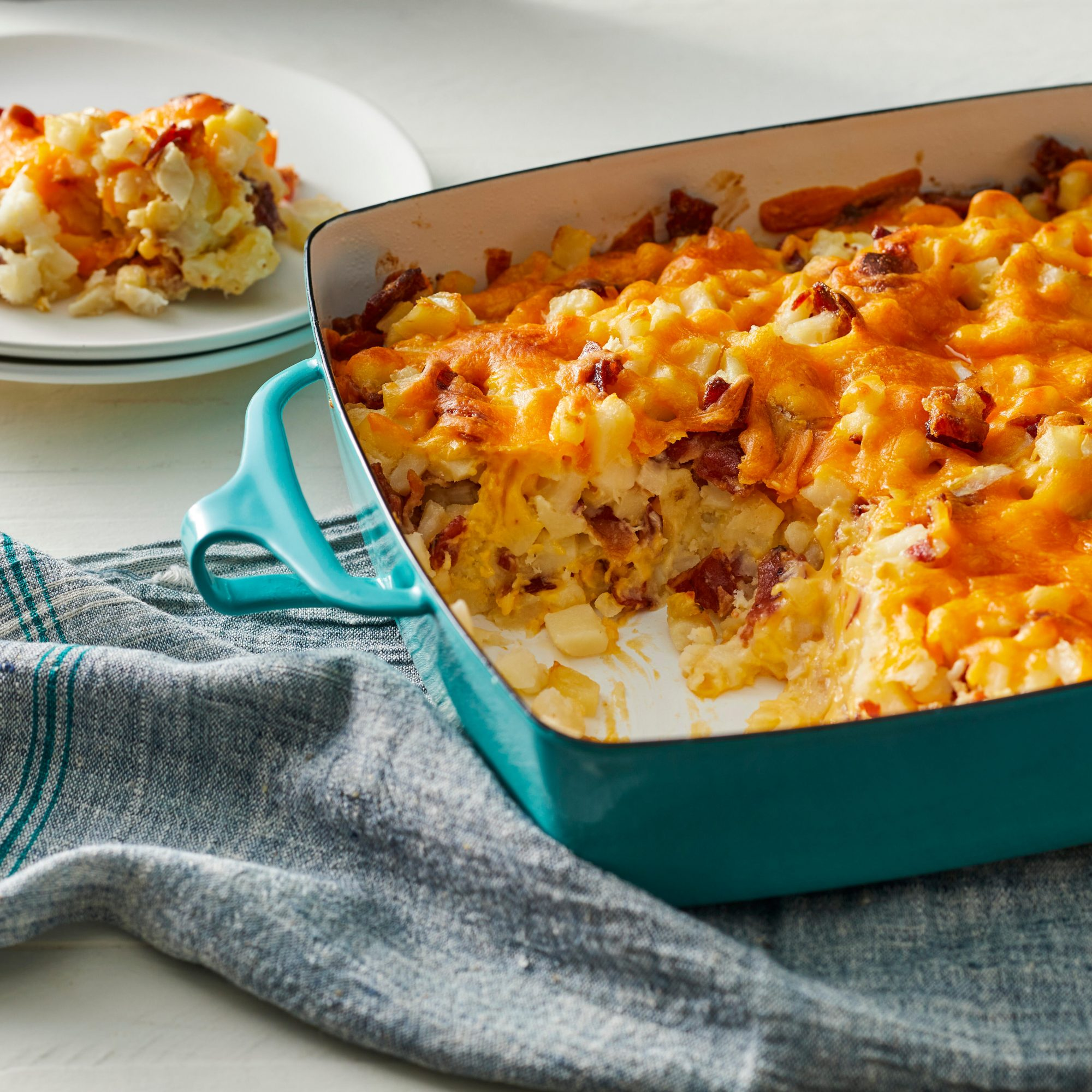Brunch potato casserole in a teal casserole dish with a serving scooped out