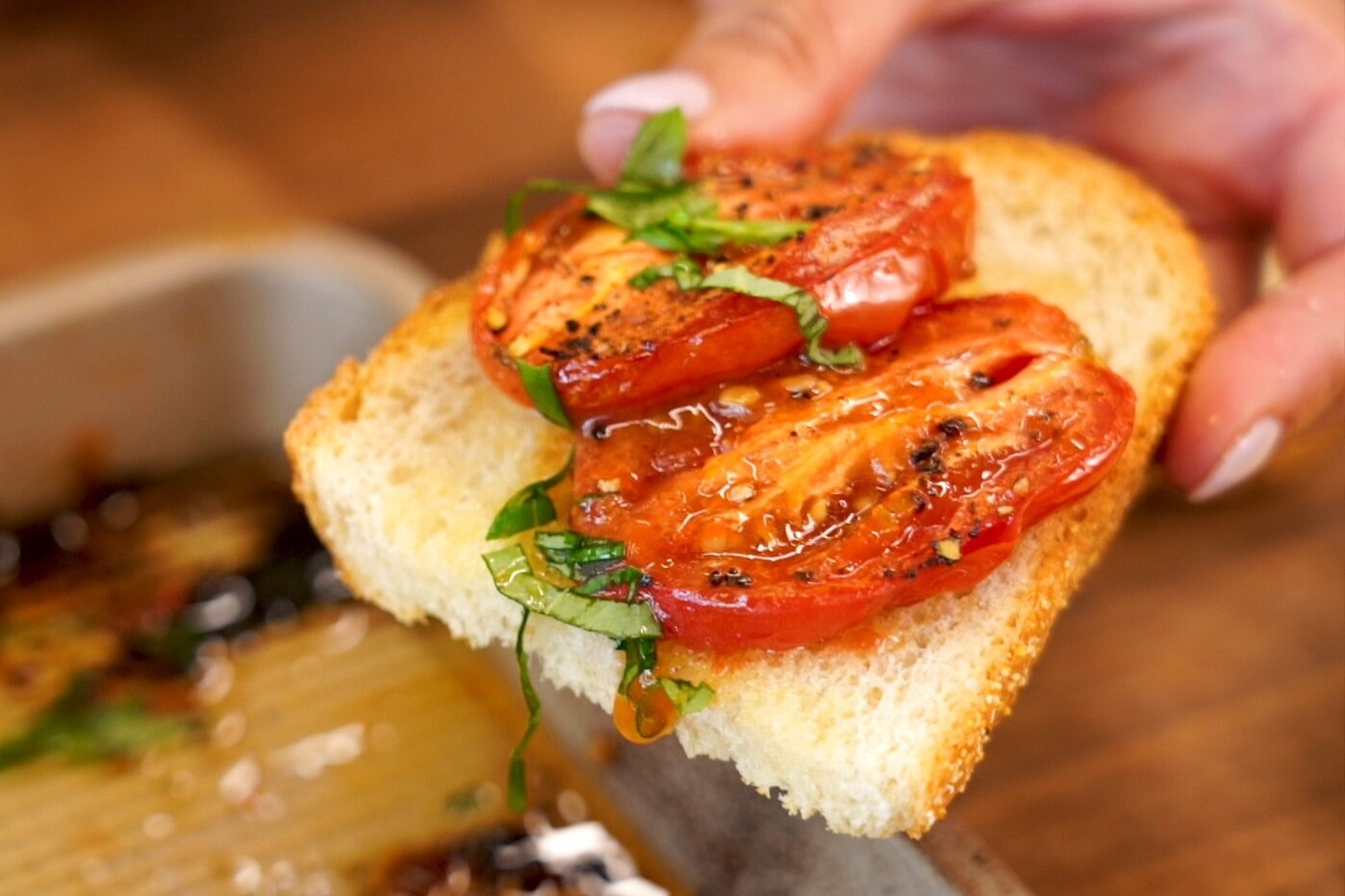 close up of homemade Roasted Roma Tomatoes and Garlic served on sliced bread and topped with basil