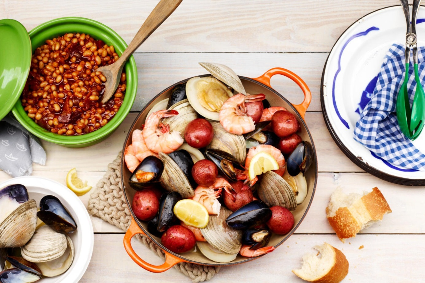 overhead view of a seafood menu with boiled shrimp, clams, mussels, and potatoes served with baked beans and bread