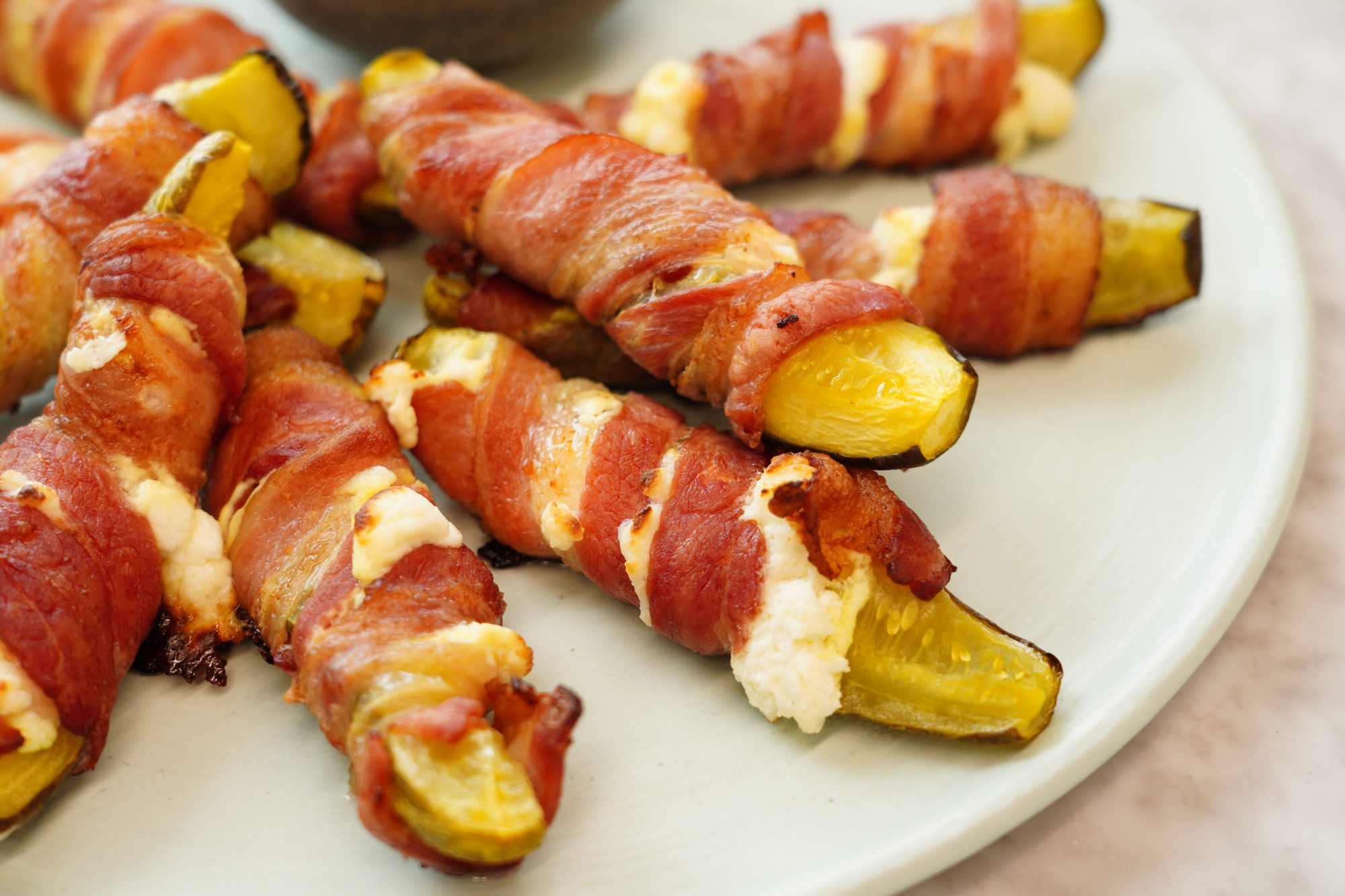 a plate of Bacon-Wrapped Pickles with cream cheese