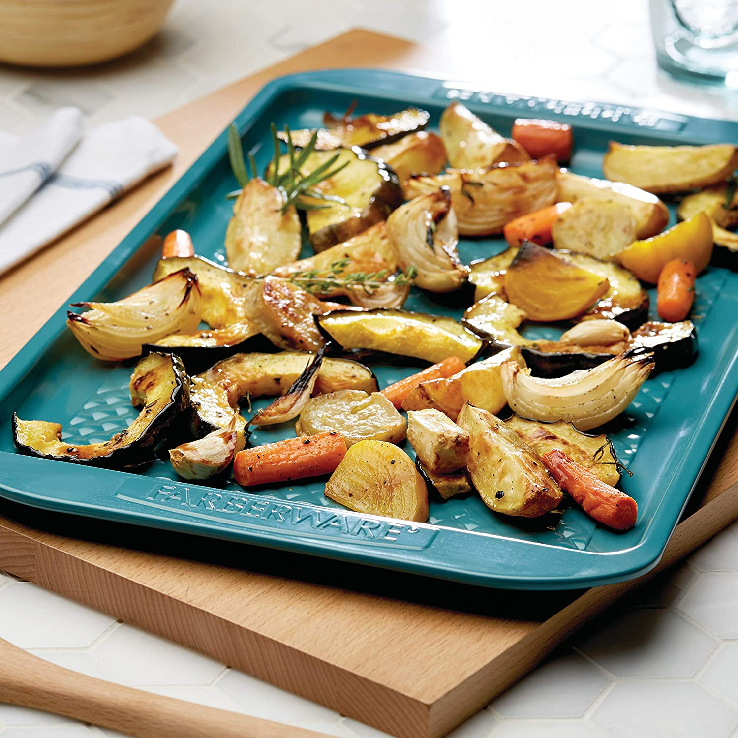 teal cooking sheet with potatoes, onions, and carrots