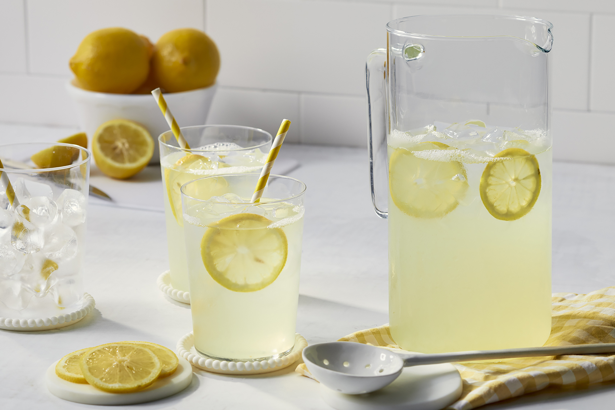A pitcher and two glasses of old fashion lemonade sit on a white kitchen counter