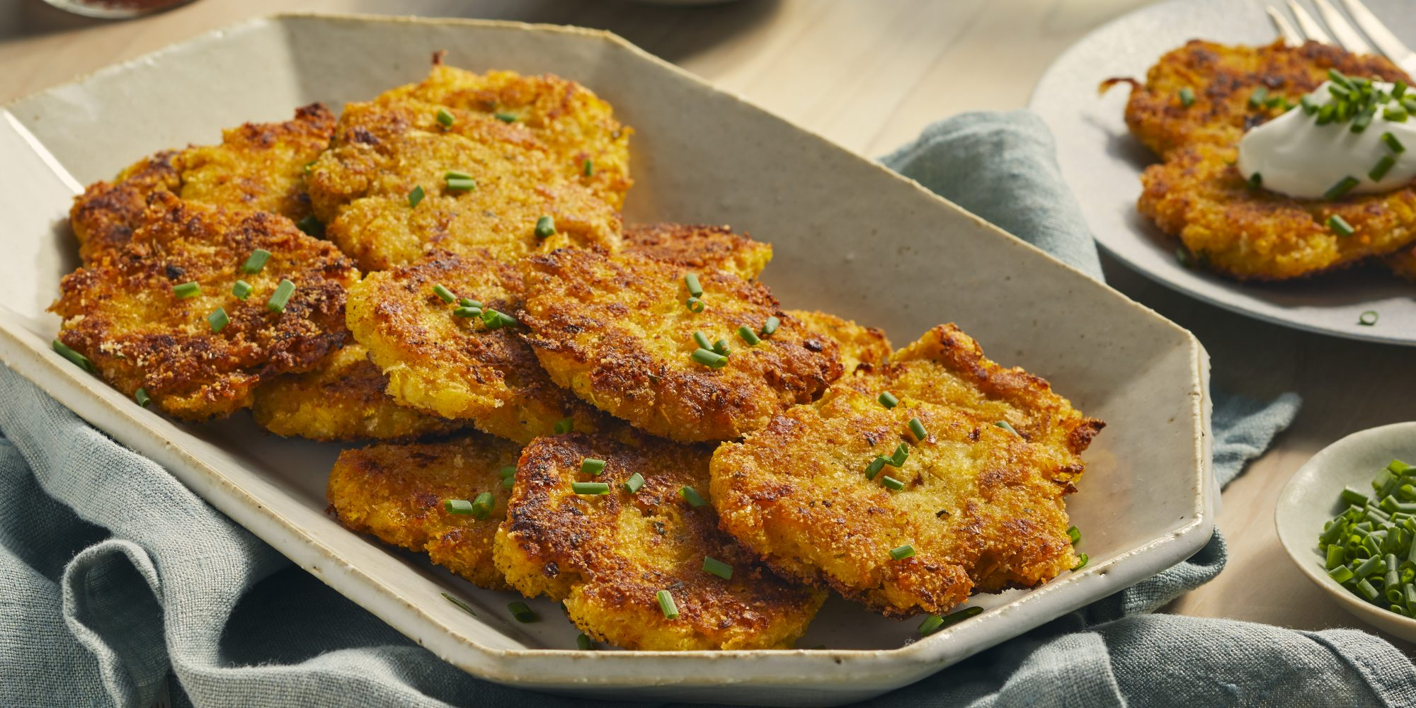 family style serving of yellow squash patties garnished with fresh chives
