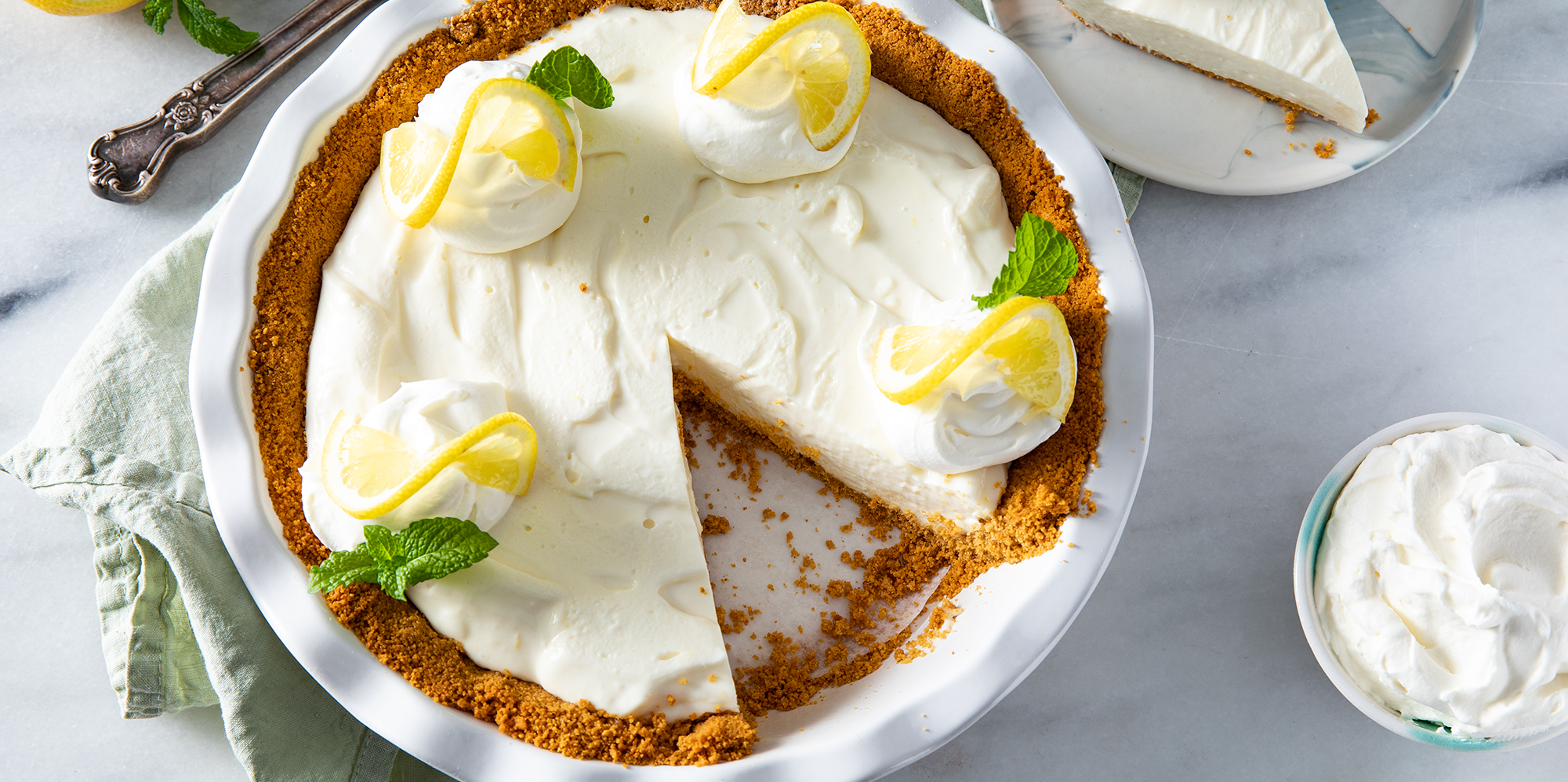 Overhead on a lemon icebox pie with a slice out and plated nearby. The pie is garnished with fresh lemon and mint.
