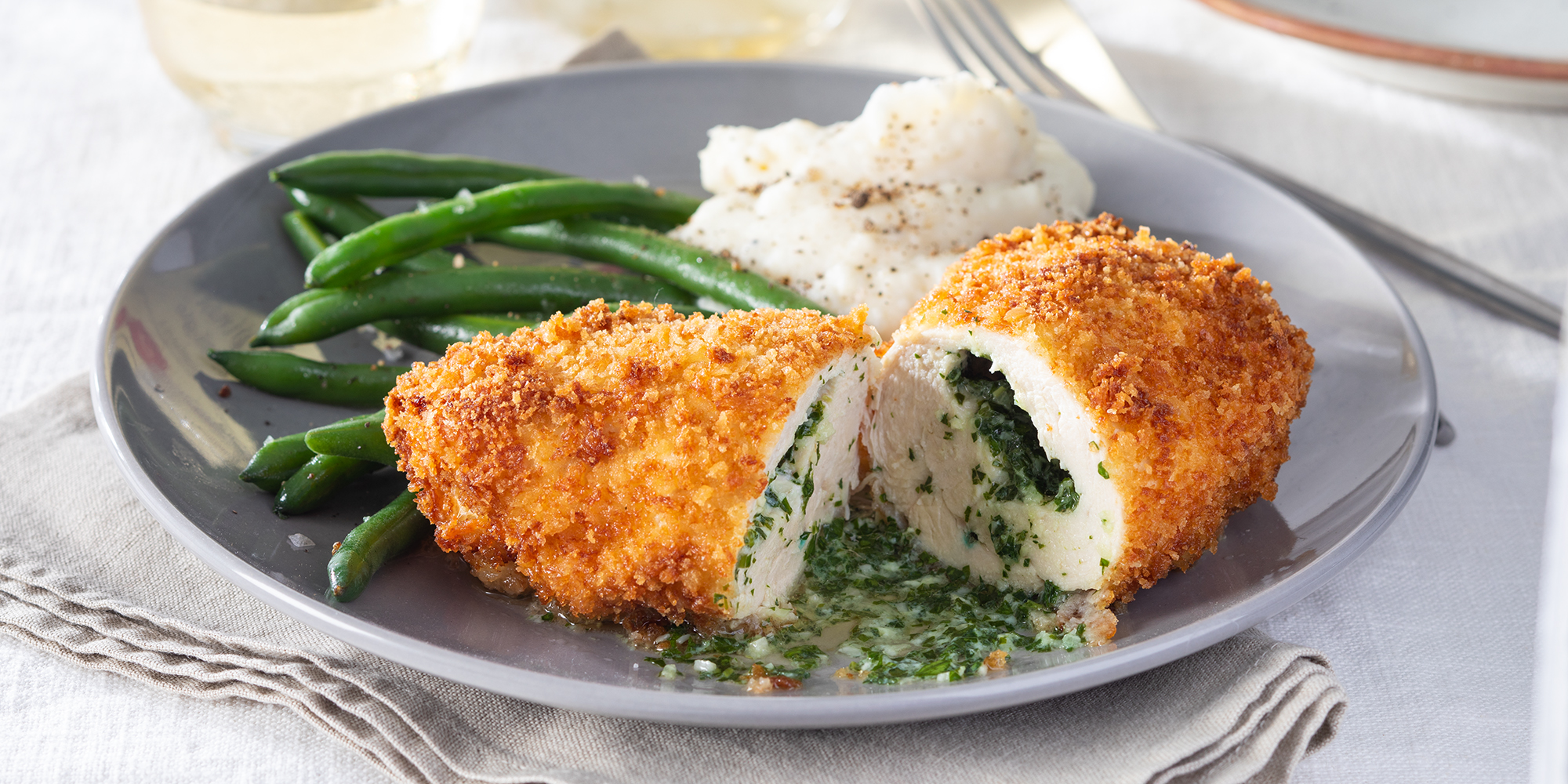 Chicken Kiev cut in half to reveal the bight herbs inside. Served with green beans and mashed potatoes