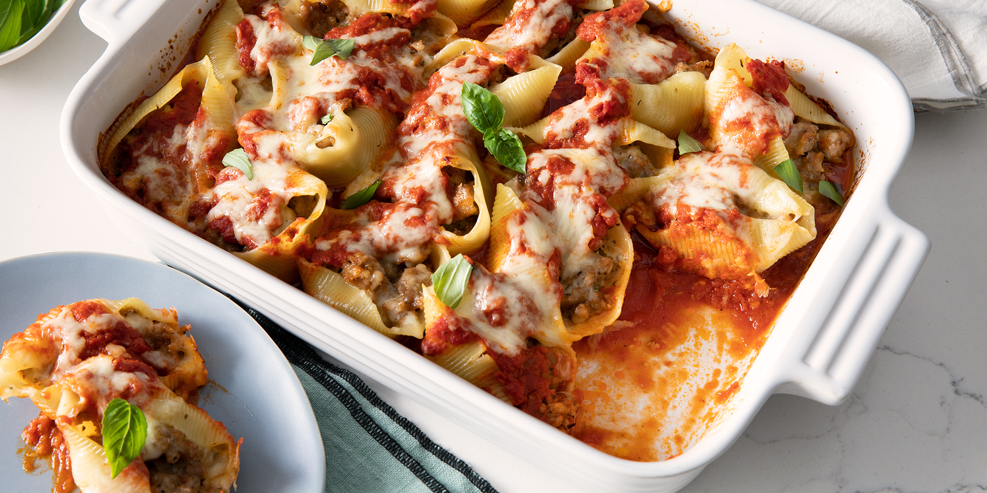 Looking into the corner of a white casserole dish of Italian stuffed shells. The casserole is garnished with fresh basil and has a scoop removed and plated.