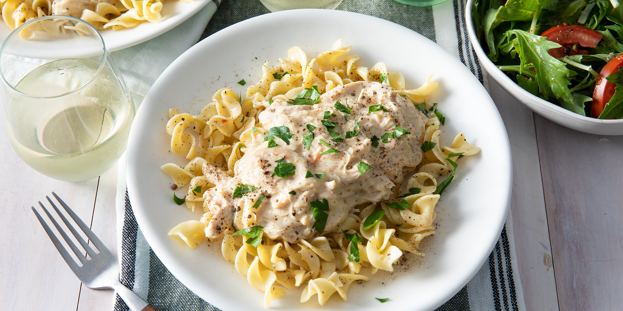 Looking down on a serving of slow-cooker chicken tetrazzini served over egg noodles and garnished with fresh chopped parsley. Served with a green salad and glass of white wine.