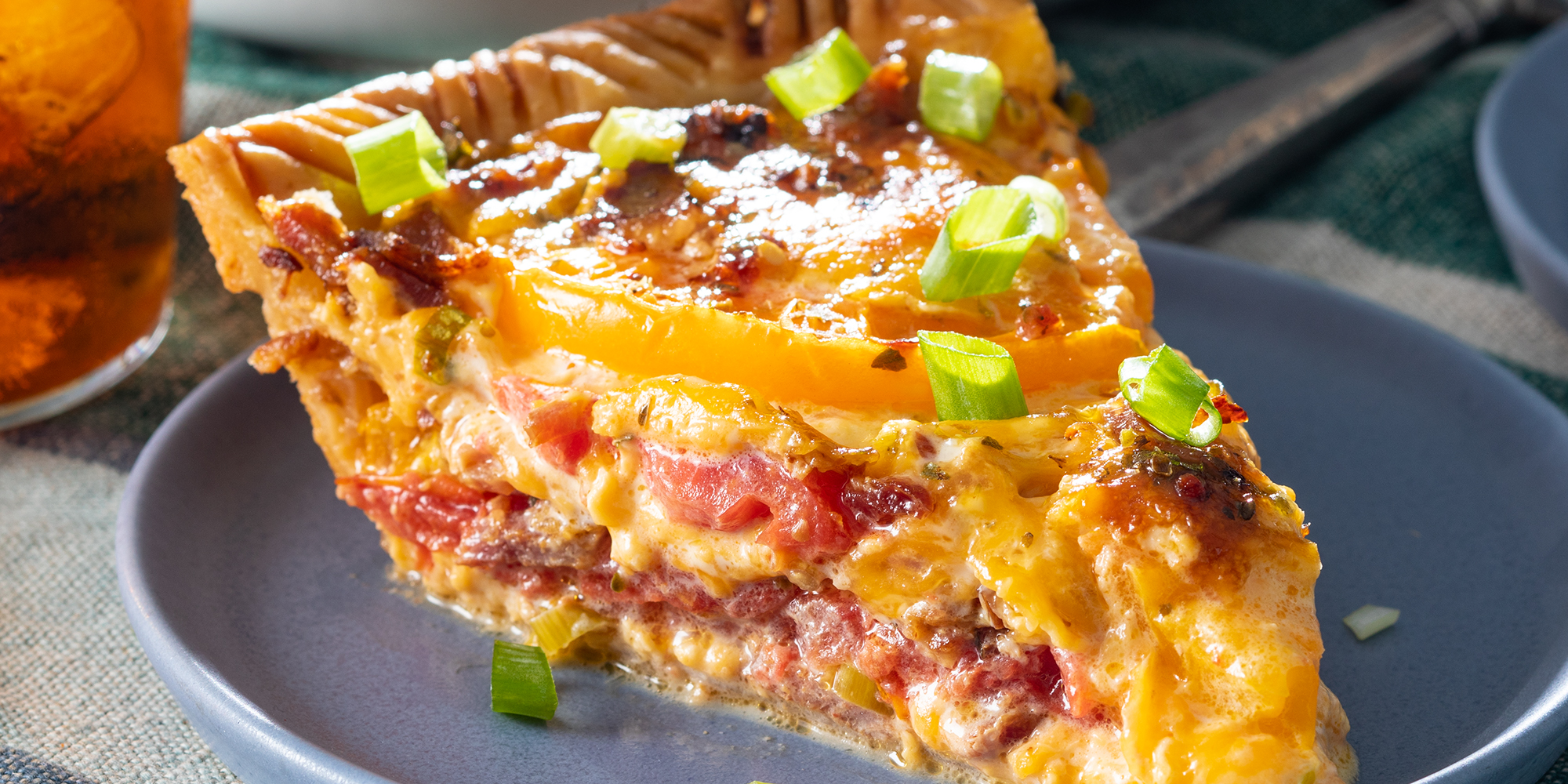 view into a slice of cheesy tomato pie topped with green onions.