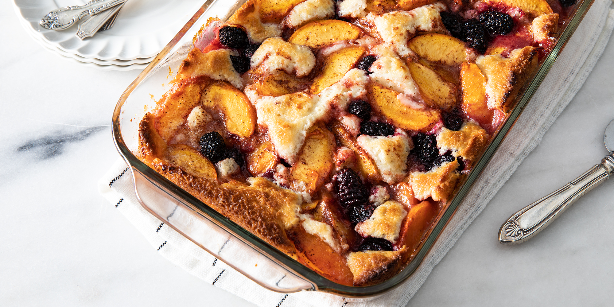 Looking down on a golden-brown peach and blackberry cobbler ready to be served.