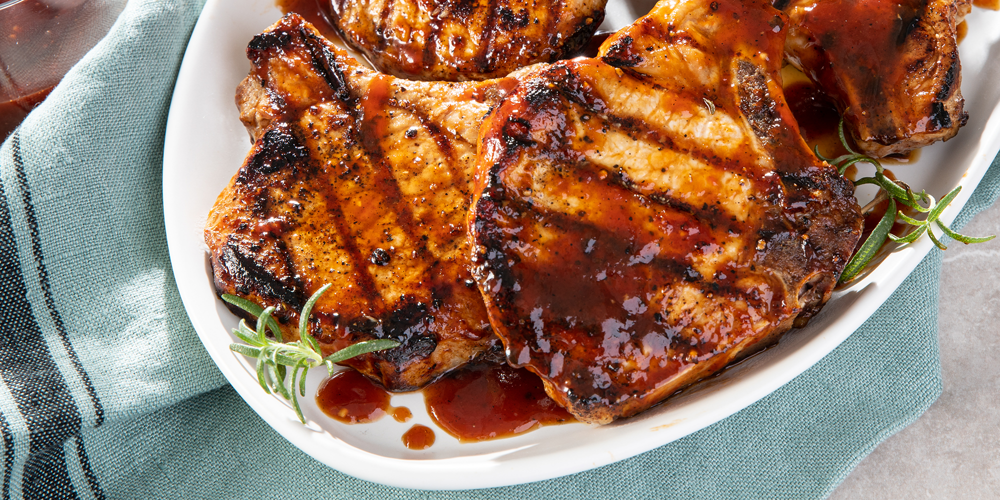 Family style platter of World's Best Honey Garlic Pork Chops garnished with extra sauce and fresh herbs.
