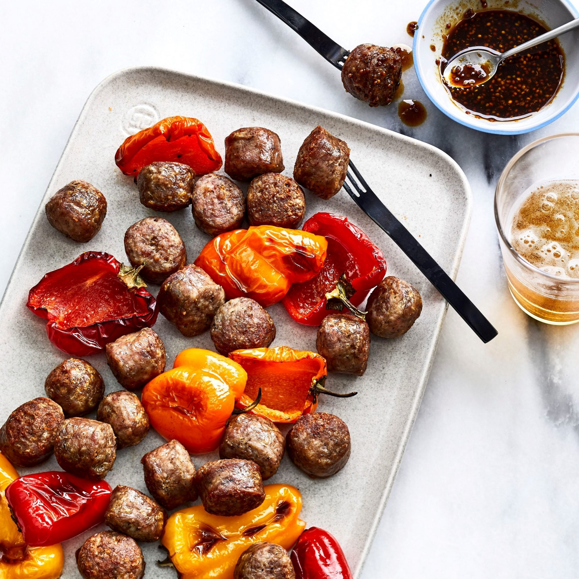 overhead view of Air-Fried Bratwurst Bites with Spicy Beer Mustard served with roasted peppers