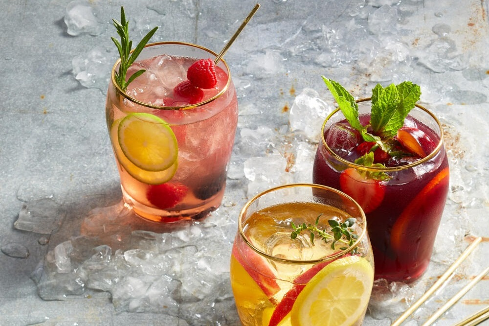 three glasses of homemade sangria with fruit and herbs