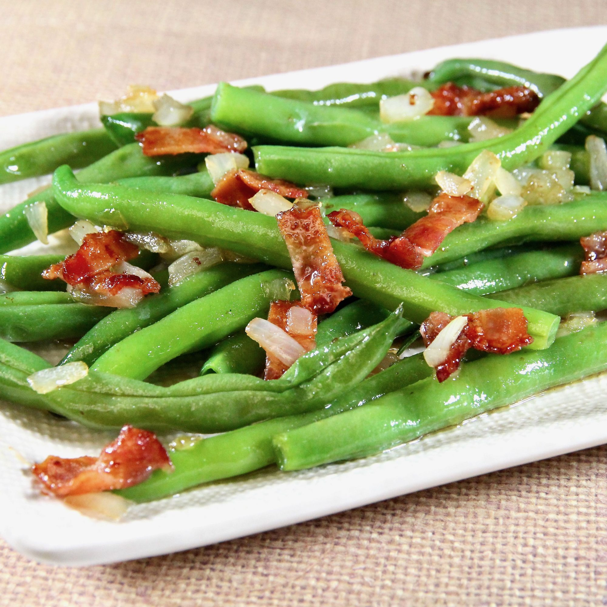 green beans with bits of bacon on a white plate