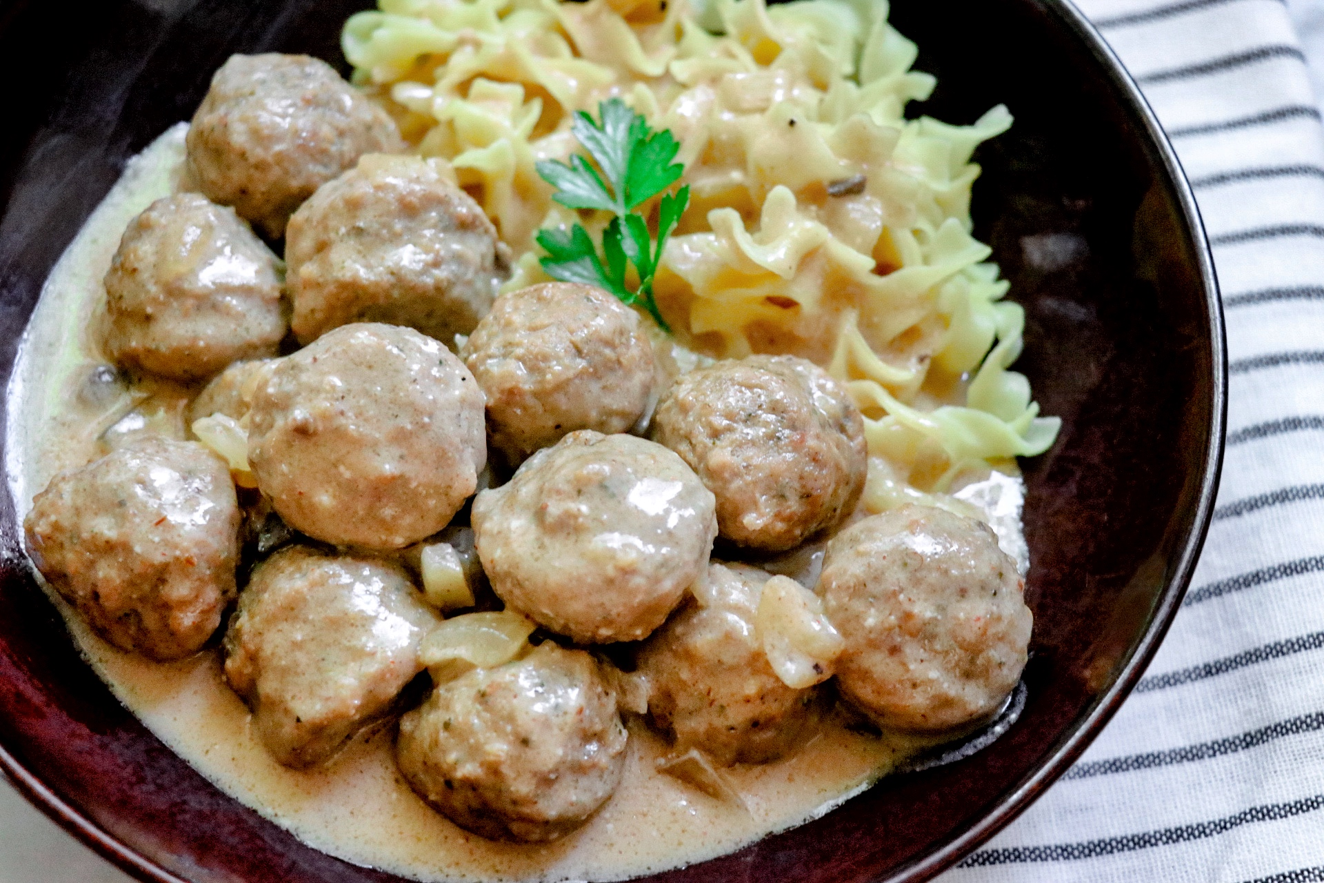 overhead view of a bowl of homemade Easy Slow Cooker Swedish Meatballs served with egg noodles