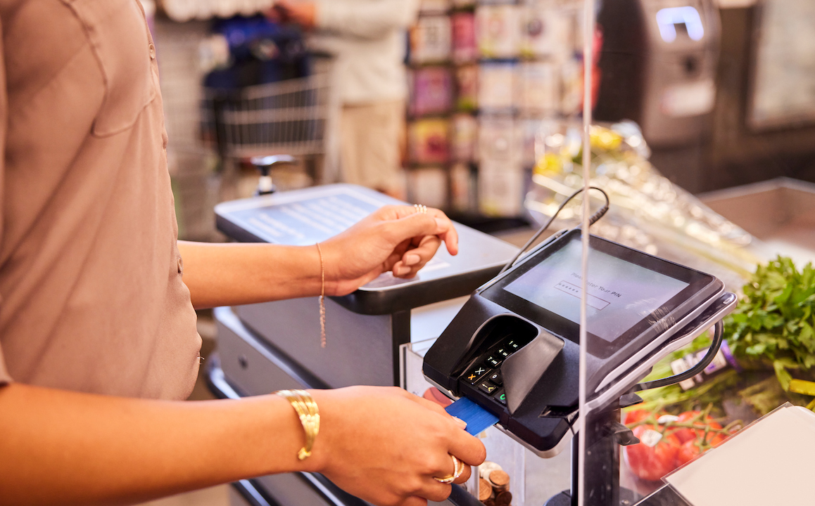 Woman paying for groceries at a plexiglass protected grocery store checkout