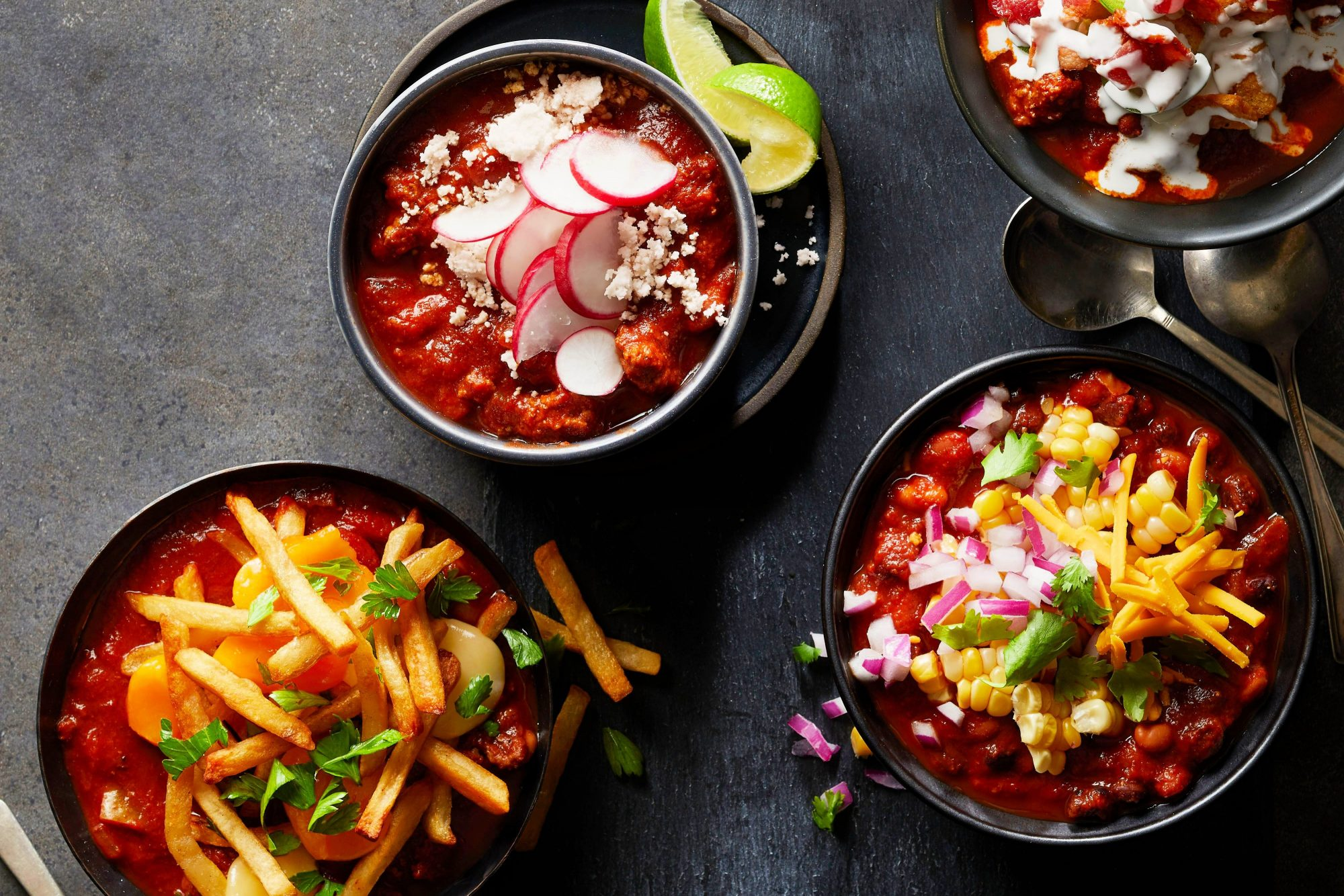 bowls of chili garnished with an array of toppings