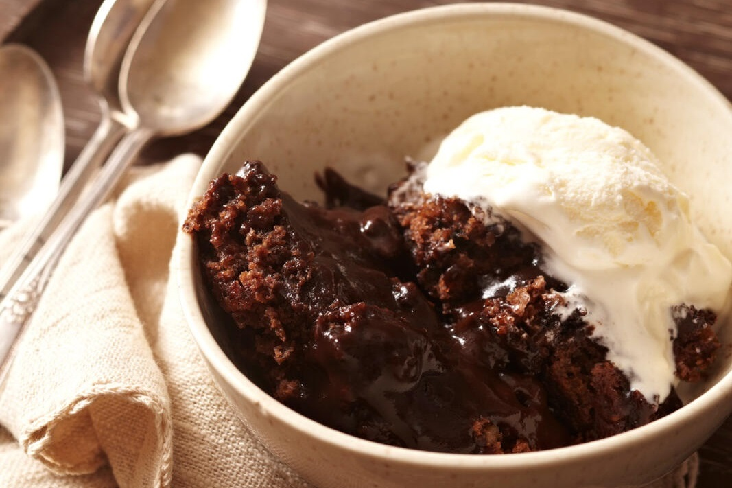 close up of a bowl of homemade chocolate pudding cake served with a scoop of vanilla ice cream