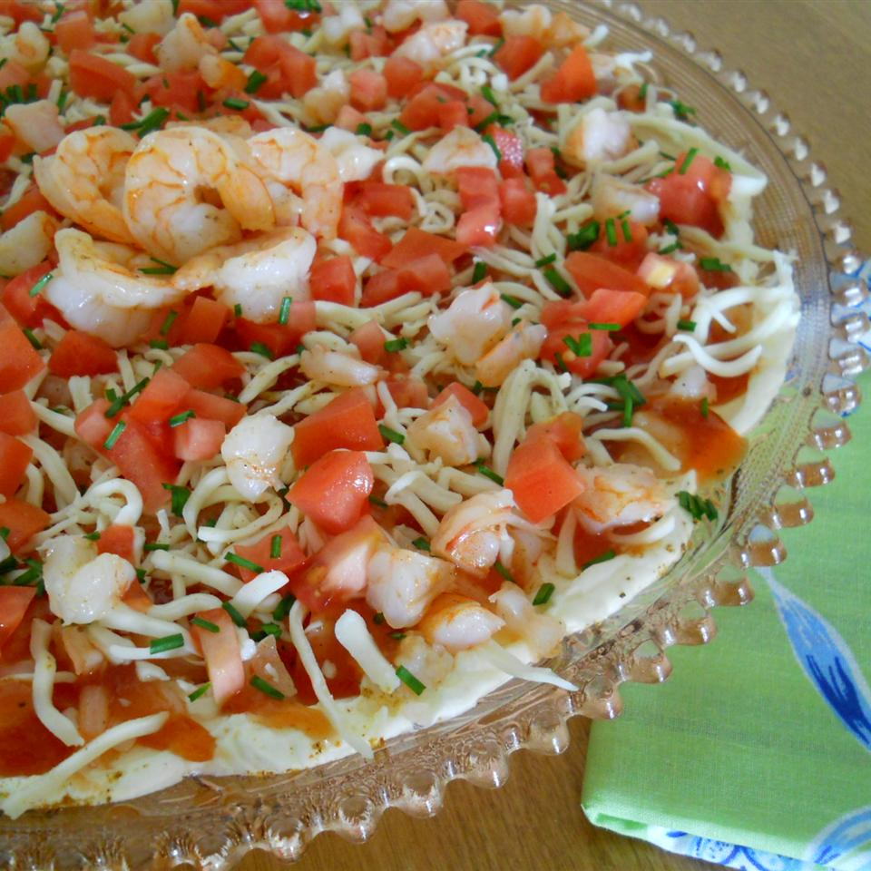 bowl of shrimp dip with shrimp, shrimp cocktail, tomatoes, shredded mozzarella, and minced scallions on a cream cheese base