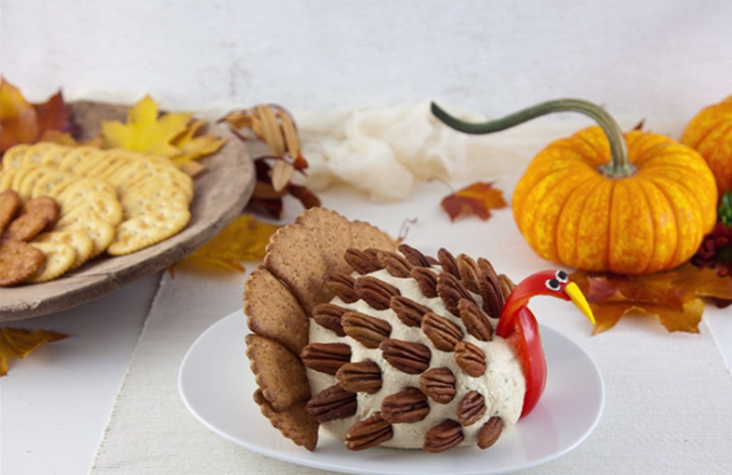 cheese ball shaped like a turkey with crackers in background