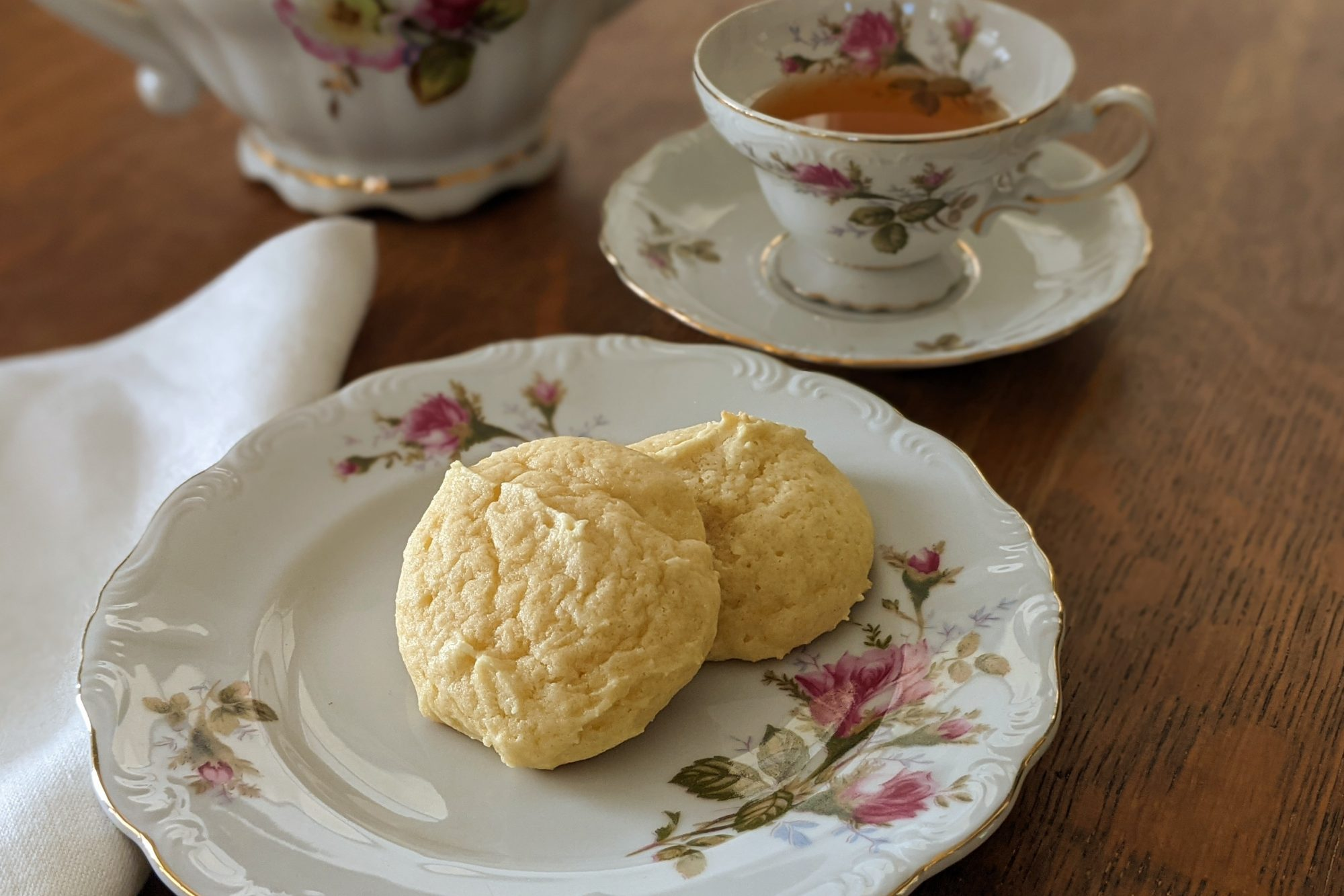 Great-Grandma's Sour Cream Drop Cookies on a plate served with a cup of tea