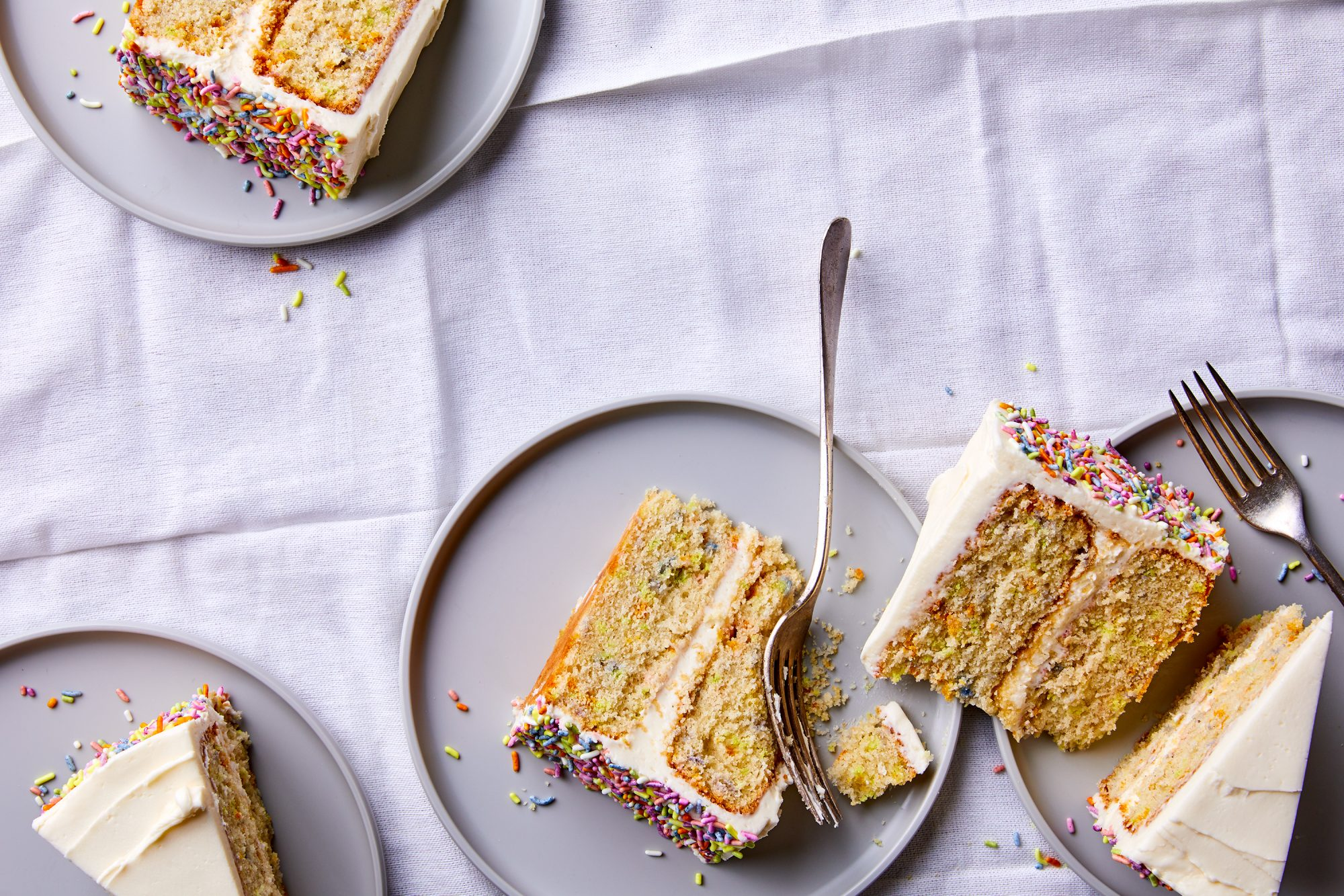 slices of birthday cake on plates on purple tablecloth
