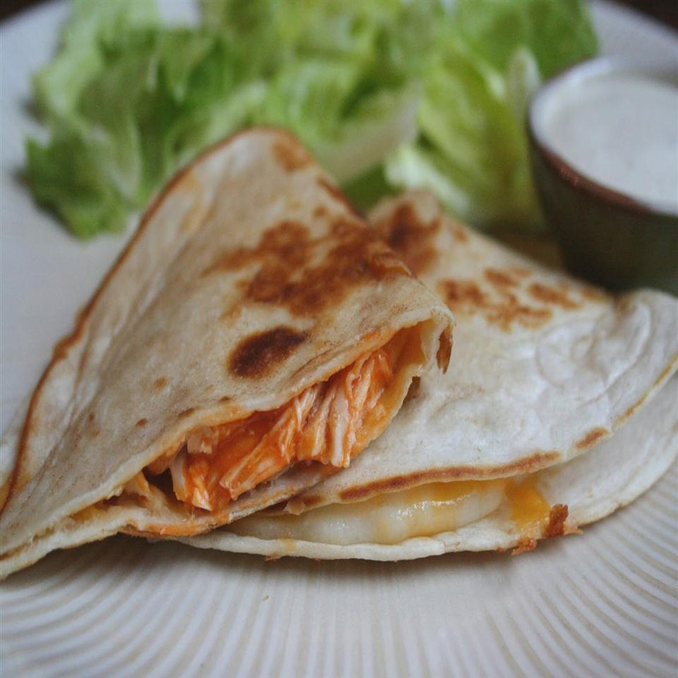 """In this five-ingredient recipe, chicken is slow cooked with red enchilada sauce and taco seasoning to make a delicious filling for quesadillas. """"I made it two days in a row. [It] was so good!"""" says reviewer Vicki Olson. Serve with a little salsa or guacamole on the side."""