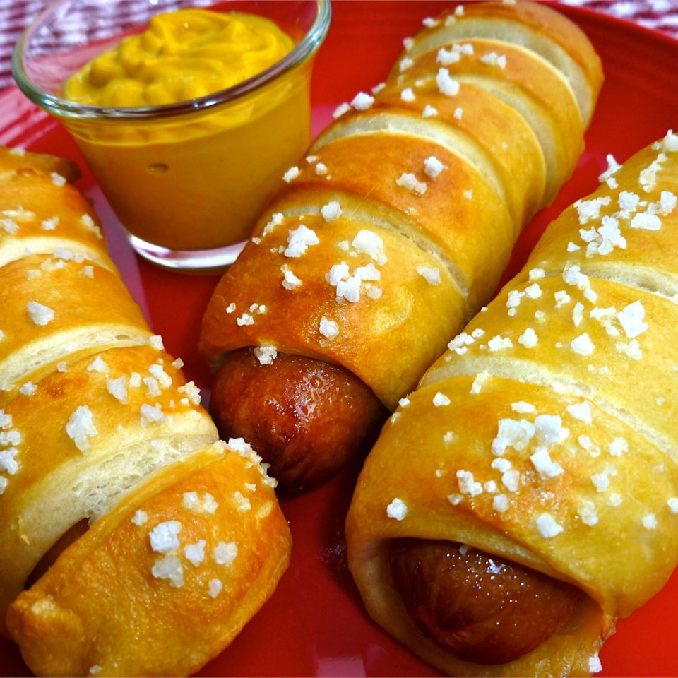Close up of a trio of Jan's Pretzel Dogs - hot dogs rolled and baked in pretzel dough - with mustard dipping sauce