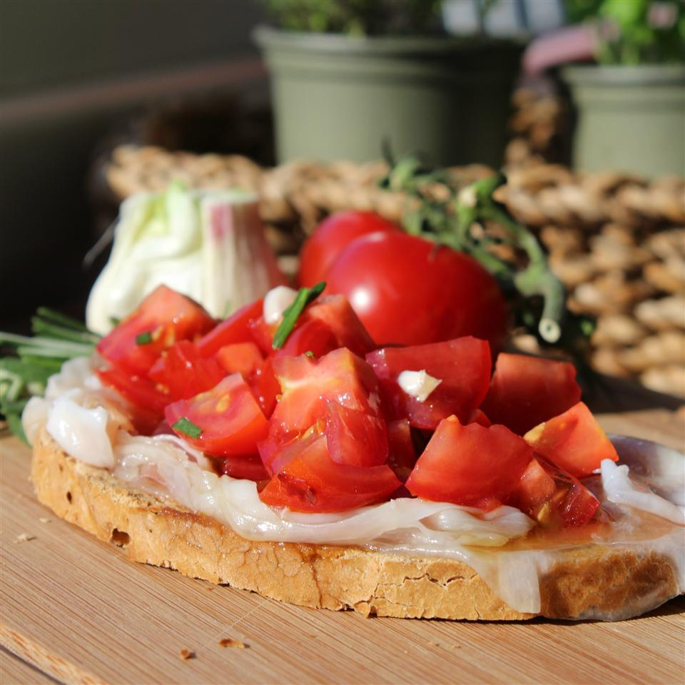 closeup of a slice of Italian bread topped with thin slices of lardo and chopped tomatoes