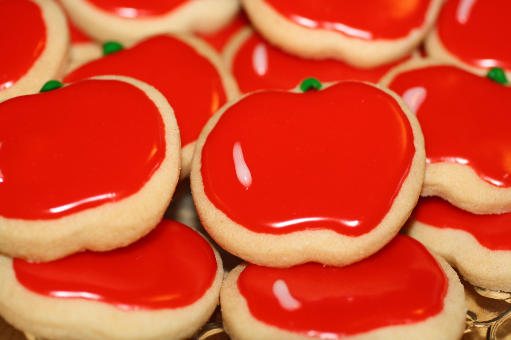 apple-shaped sugar cookies decorated with shiny red frosting