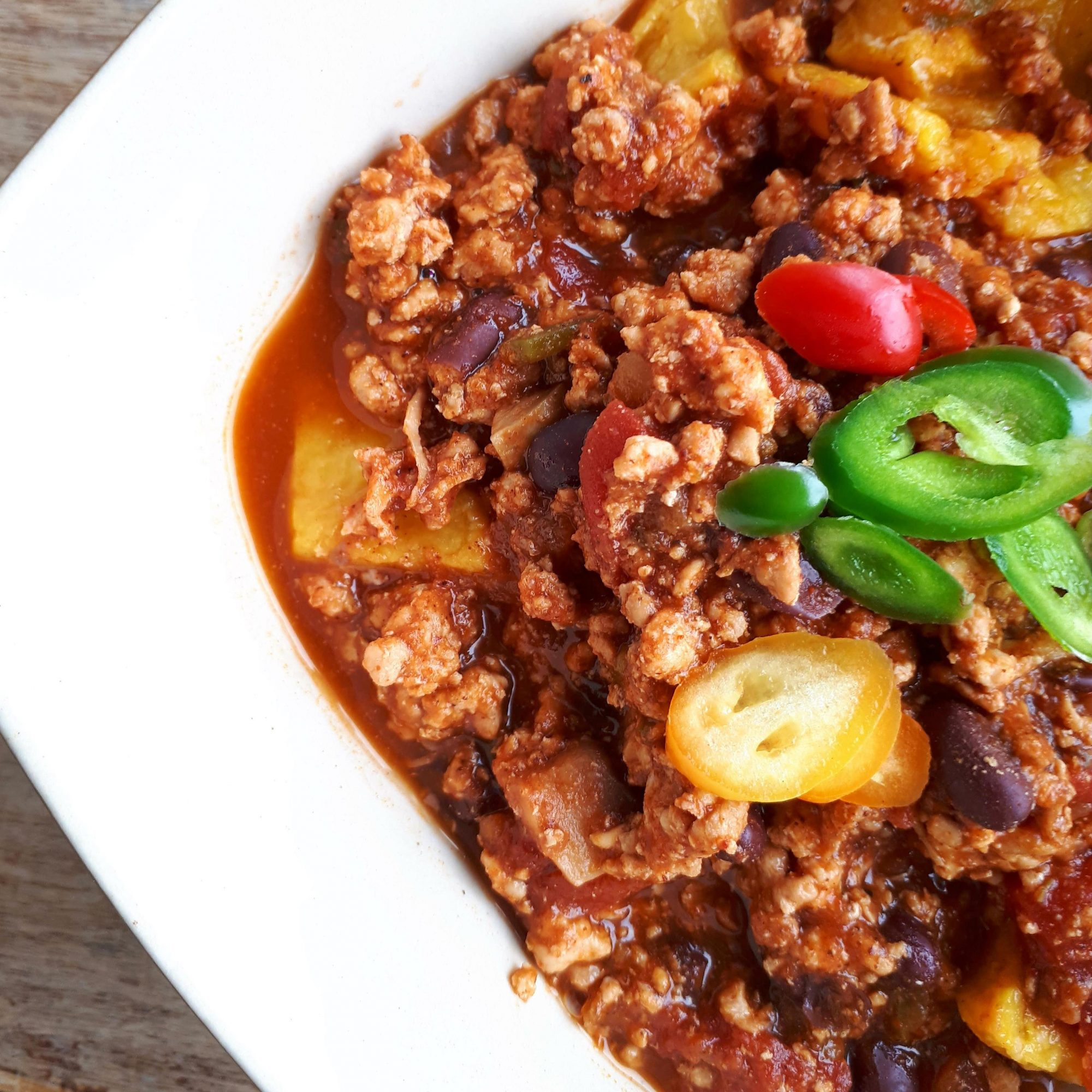 ground turkey and pumpkin chili topped with jalapeno slices in a white bowl