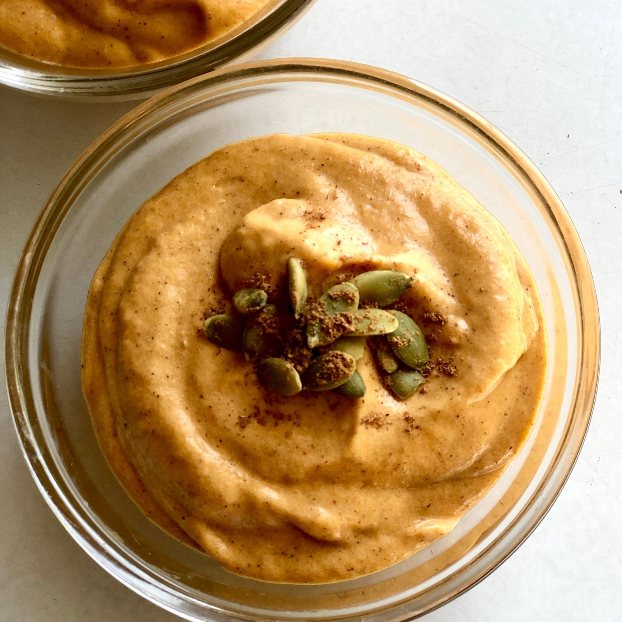 single serving of homemade Skinny Pumpkin Pie Pudding garnished with pumpkin seeds and grated nutmeg