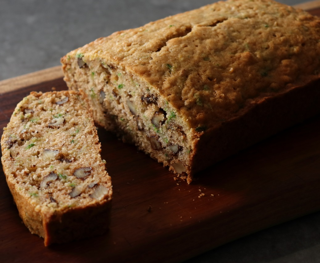 a loaf of zucchini bread at an angle with a slice cut out of it, displayed on a wooden cutting board