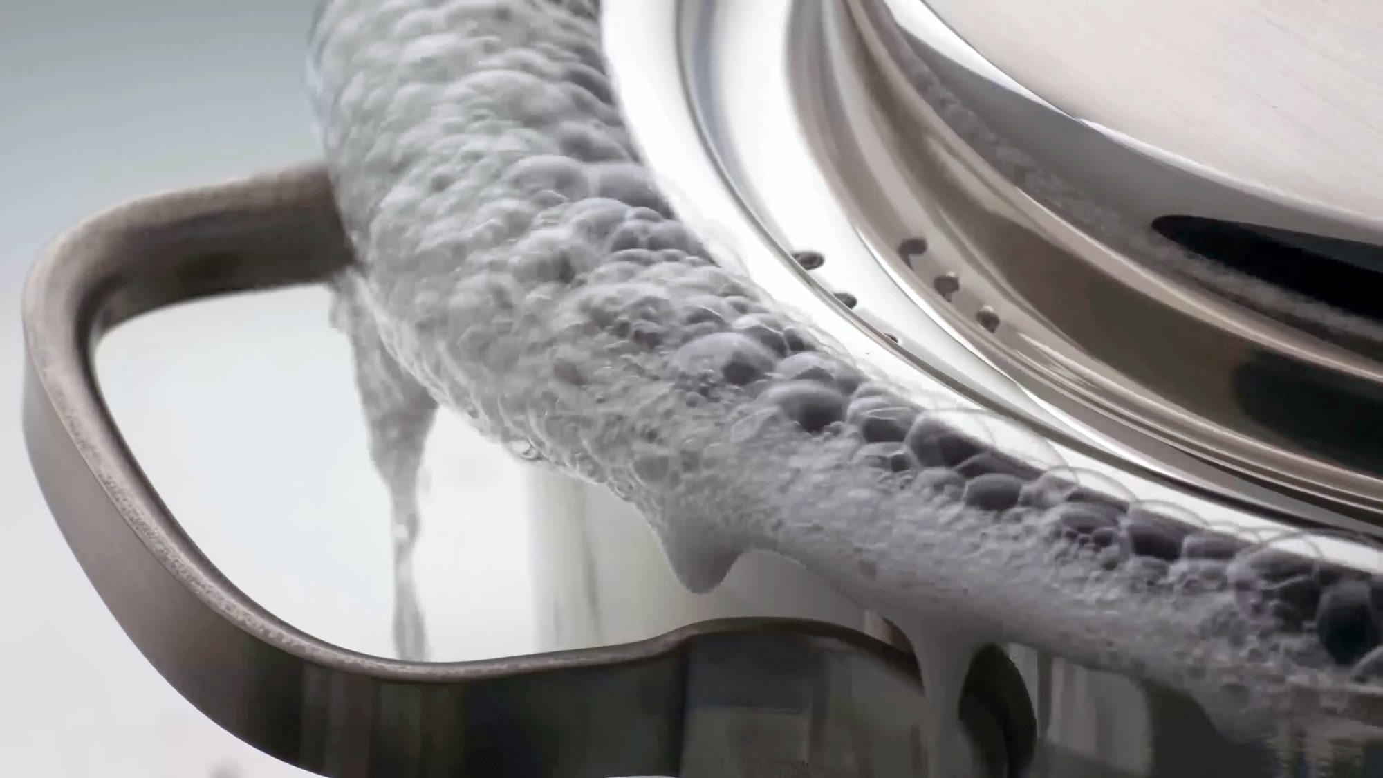 Water boiling over from a saucepan with lid. Pot boiling over. close up